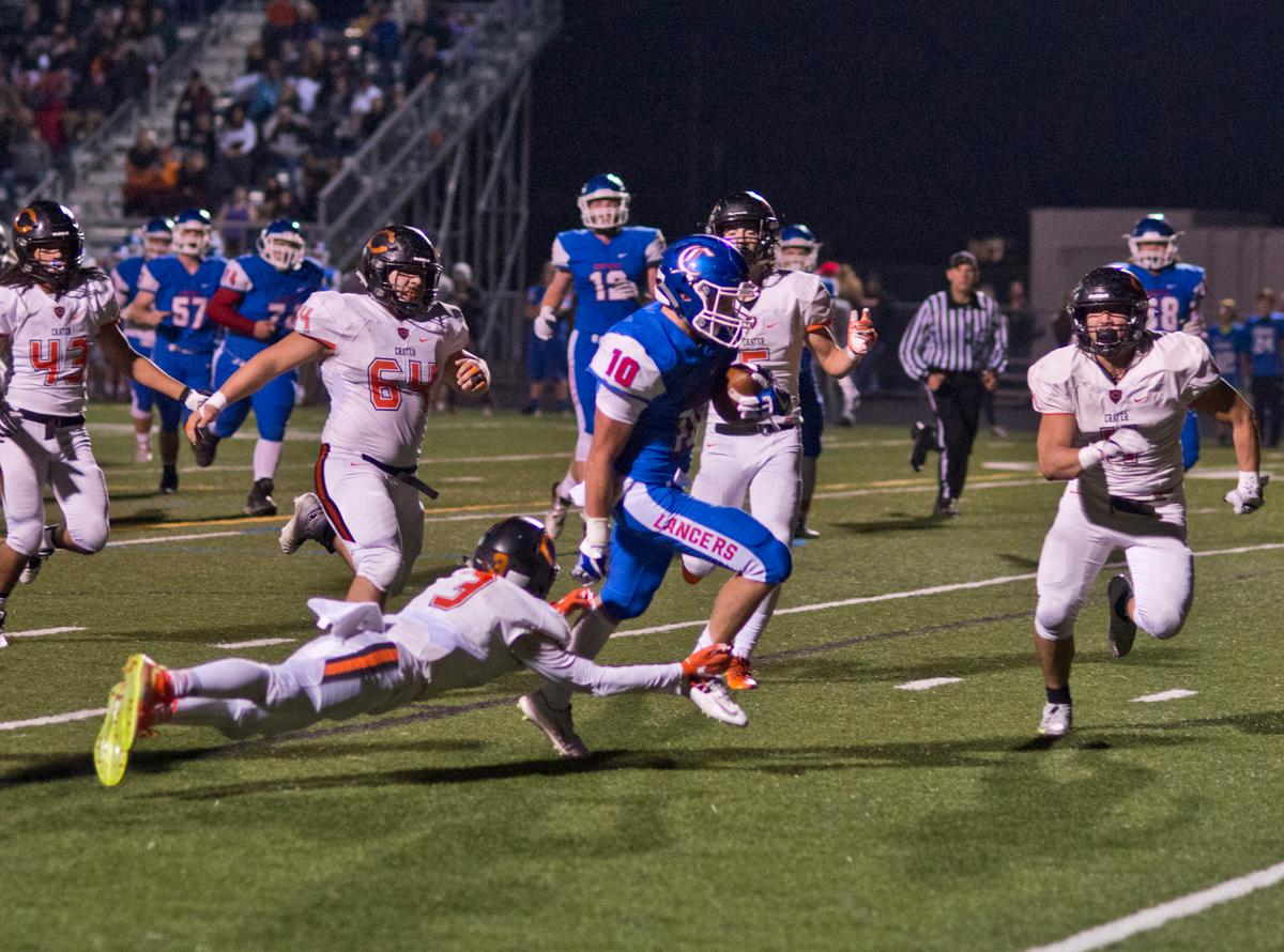 Churchill Lancers running back Tyson Bennion (#10) attempts to shake free from Crater Comets linebacker Bailee Robles (#3). Churchill defeated Crater 63-21 on Friday at their homecoming game. Churchill remains undefeated with a conference record of 9-0. Photo by Dan Morrison, Oregon News Lab