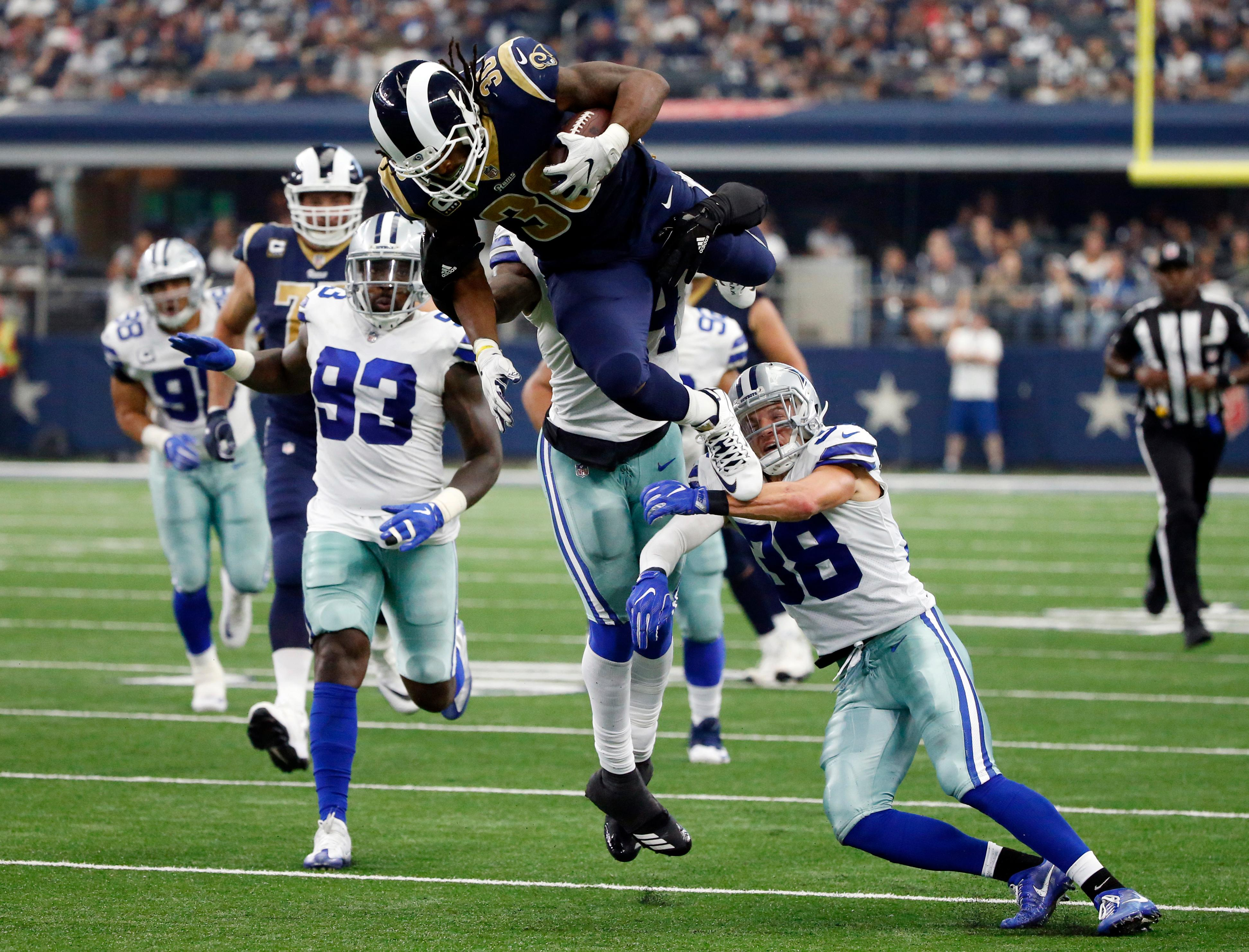 Los Angeles Rams running back Todd Gurley (30) is stopped by Dallas Cowboys linebacker Jaylon Smith, rear, and safety Jeff Heath (38) after Gurley lept over Heath on a carry in the second half of an NFL football game, Sunday, Oct. 1, 2017, in Arlington, Texas. (AP Photo/Michael Ainsworth)