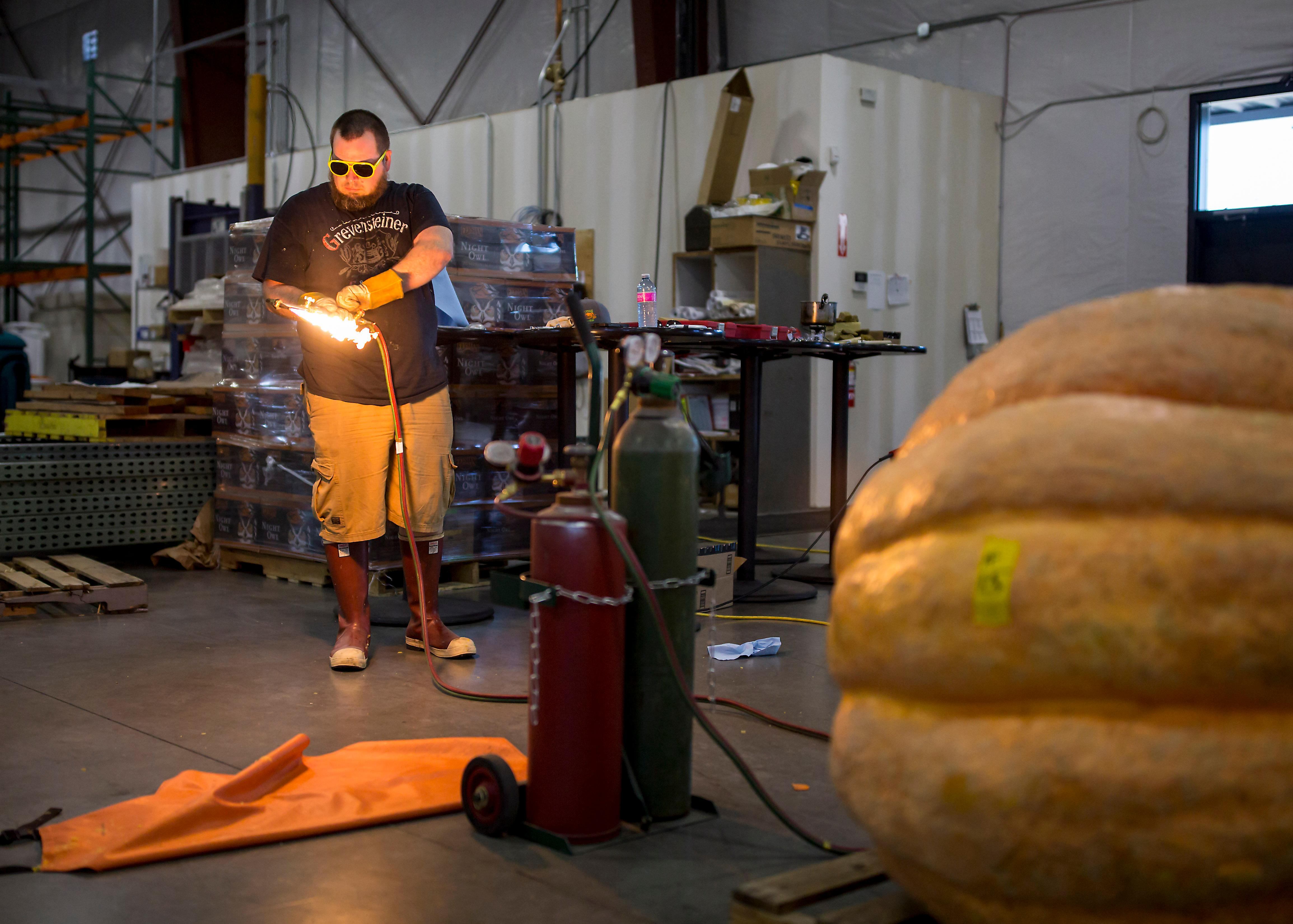 Elysian cellarmaster Dan-o slowly transforms a massive pumpkin into a usable keg for the Great Pumpkin Beer Festival that will take place this weekend at the Seattle Center. (Sy Bean / Seattle Refined)