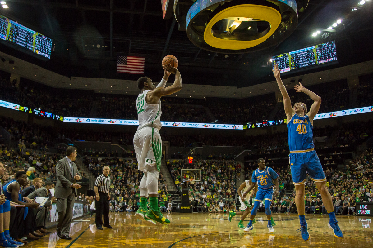 Oregon forward MiKyle McIntosh (#22) shoots a 3-pointer over UCLA center Thomas Welsh (#40). The Oregon Ducks men's basketball team defeated the UCLA Bruins 94-91 Saturday night in front of a home crowd at Matthew Knight Arena. The win brings the Ducks 13-7 overall for the season and 3-4 in Pac-12 play. Photo by Dillon Vibes