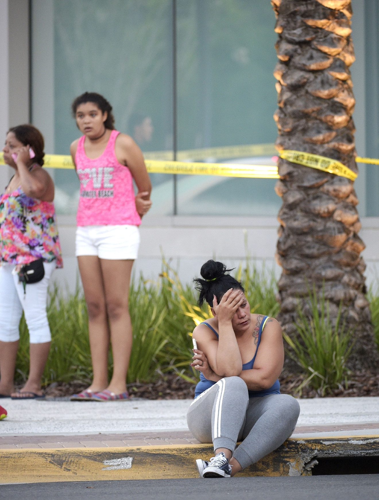 People wait outside the emergency entrance of the Orlando Regional Medical Center hospital after a shooting involving multiple fatalities at Pulse Orlando nightclub in Orlando, Fla., Sunday, June 12, 2016. (AP Photo/Phelan M. Ebenhack)