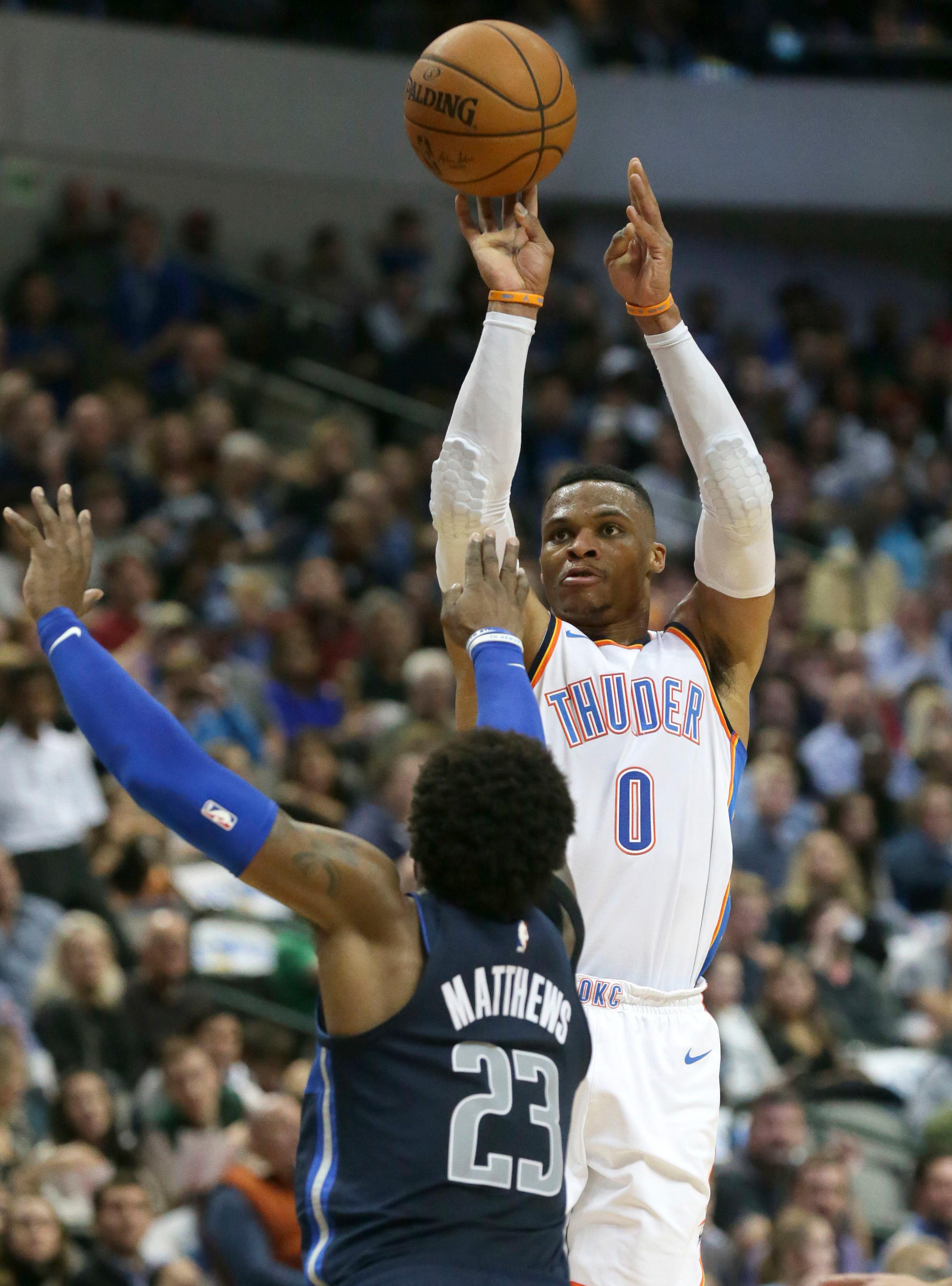 Oklahoma City Thunder guard Russell Westbrook (0) shoots against Dallas Mavericks guard Wesley Matthews (23) during the first half of an NBA basketball game in Dallas, Saturday, Nov. 25, 2017. (AP Photo/LM Otero)
