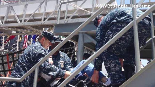 The sailors carried him and his wheelchair up the stairs.