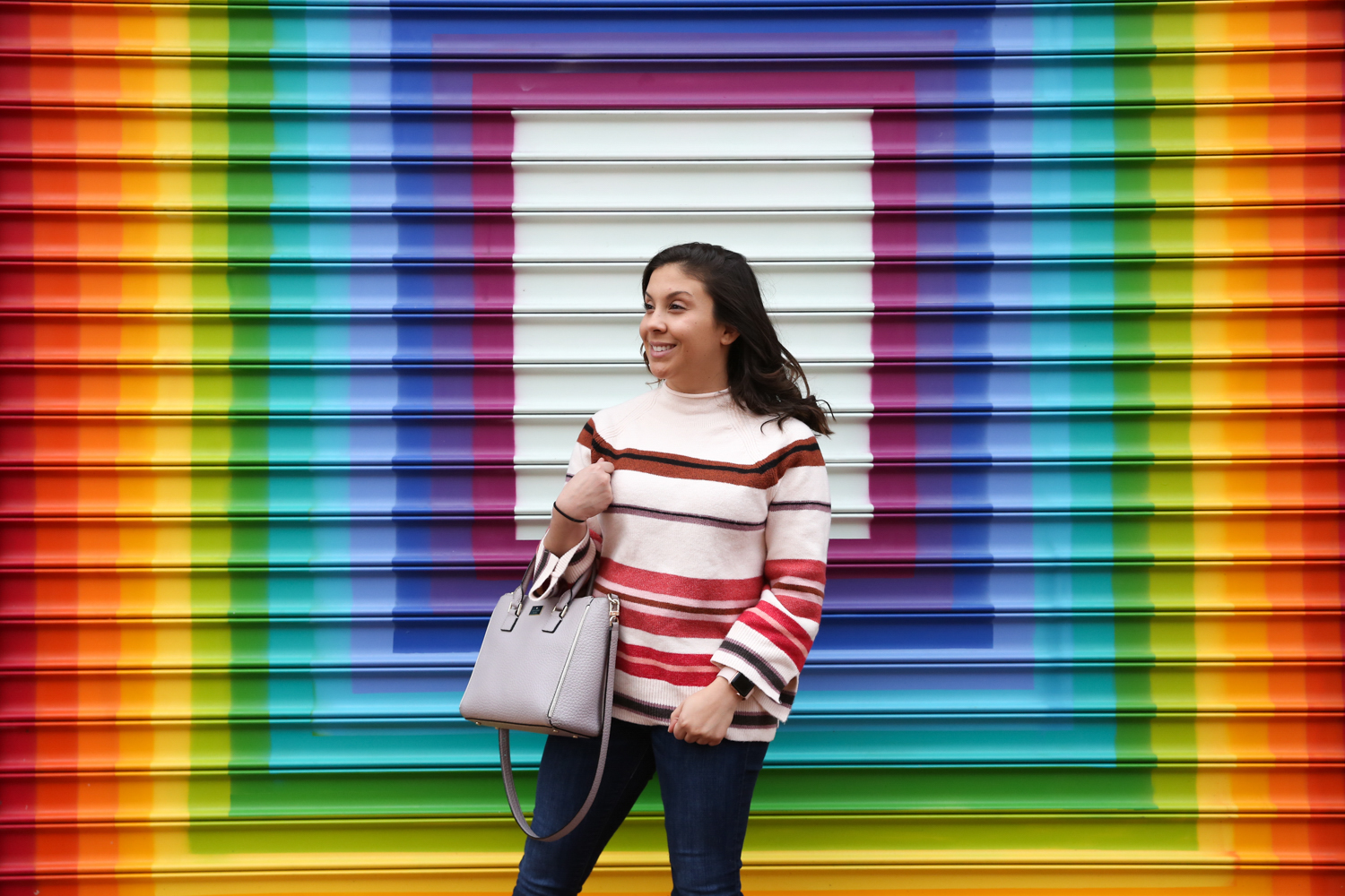 Okay, this isn't exactly candid - we were showing off the most Instagrammable walls around D.C.! but Tina Irizarry's sweater has a contemporary twist with its bell sleeves and dark stripes. (Amanda Andrade-Rhoades/DC Refined)