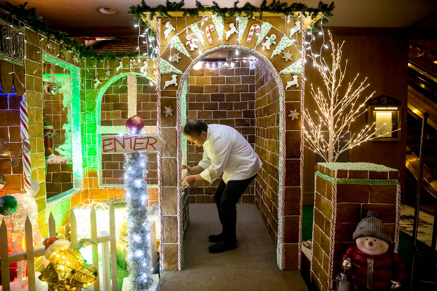 Executive pastry chef Artis Kalsons replaces candies on his lifesize gingerbread house after hungry kids picked them off at the entrance of the Fairmount Olympic Hotel in downtown Seattle. Talk about a dream home! Well - for a person with a sweet tooth that is!The creation of this colossal Gingerbread house has been going on since August and took eight engineers, 15 culinary stars, and hundreds of helping hands. The recipe looks like this: 960 pounds of flour, 20 gallons of milk, 75 gallons of icing, 80 pounds of molasses, 80 pounds of butter, 3 pounds of cinnamon, 3 pounds of nutmeg, 170 pounds of brown sugar, 3 pounds of anise, and 3 pounds of clove! Phew. It gets better... The finished product has 4,100 Gingerbread tiles, 2,500 candy canes, 1,000 spearmints, 50 pounds of crushed candy and 144 feet of candy ropes. I think we just got a sugar contact high. If you haven't ventured down there, this gingerbread house in a must-see, folks! (Image: Sy Bean / Seattle Refined).