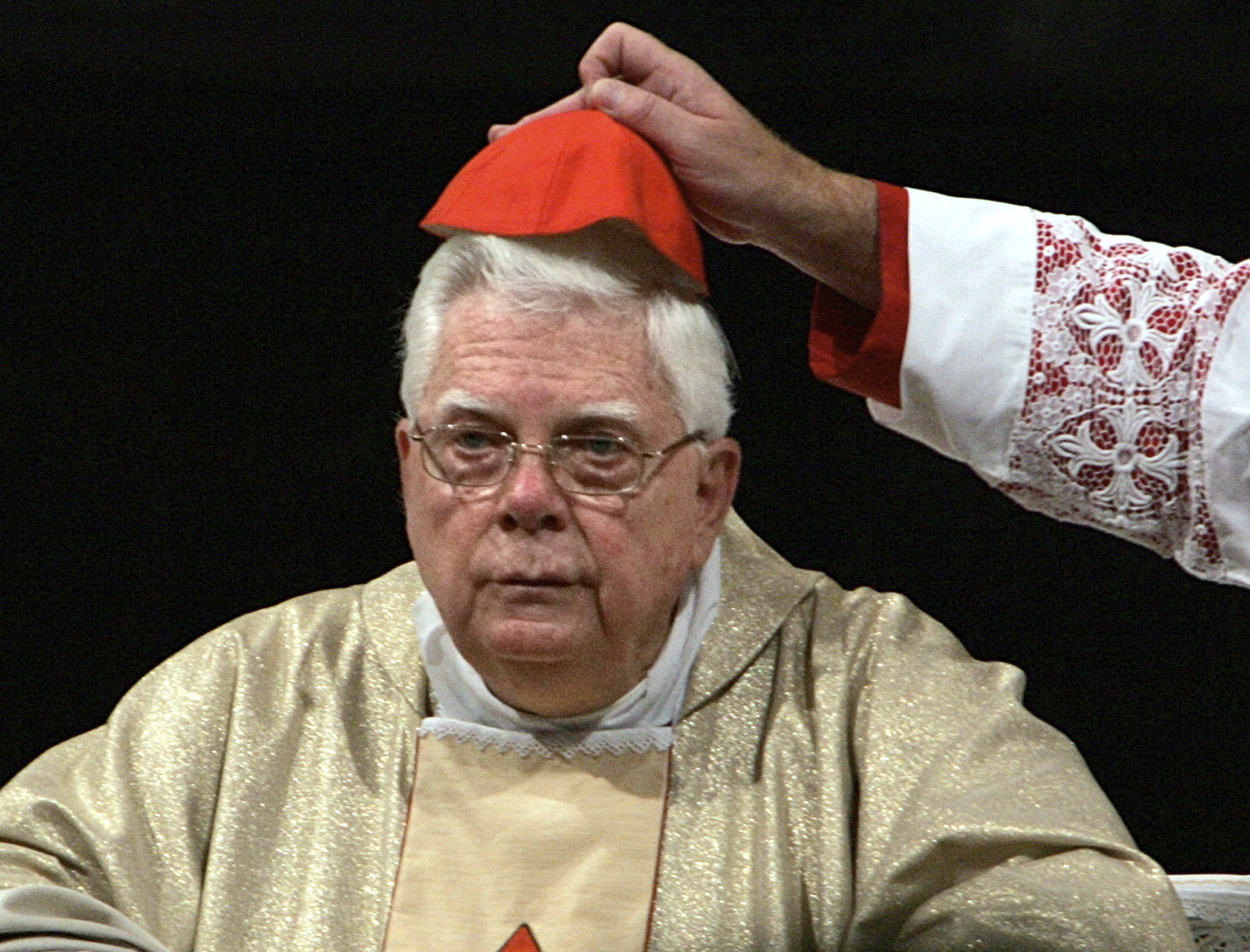 FILE - In this Thursday, Aug. 5, 2004 file photo, Cardinal Bernard Law has his skull cap adjusted during the ceremony for Our Lady of the Snows, in St. Mary Major's Basilica in Rome, Italy. An official with the Catholic Church said Tuesday, Dec. 19, 2017, that Cardinal Bernard Law, the disgraced former archbishop of Boston, has died at 86. Law recently had been hospitalized in Rome. Law stepped down under pressure in 2002 over his handling of clergy sex abuse cases. (AP Photo/Domenico Stinellis, File)