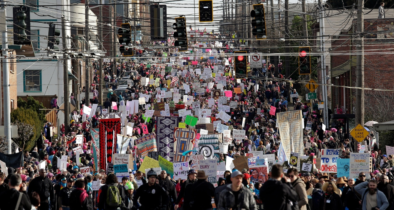EDS NOTE: GRAPHIC LANGUAGE- Tens of thousands of demonstrators fill a street headed toward downtown during a women's march Saturday, Jan. 21, 2017, in Seattle. Women across the Pacific Northwest marched in solidarity with the Women's March on Washington and to send a message in support of women's rights and other causes. (AP Photo/Elaine Thompson)