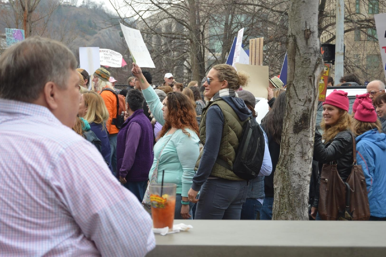 Richard Mueller sipped on a Bloody Mary as he watched marchers go by. (Photo credit: WLOS staff)