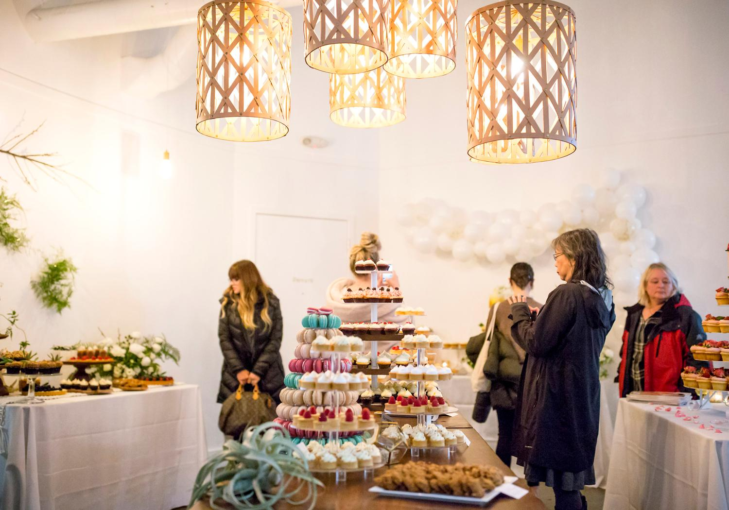 Towers of baked macarons, cupcakes, and cheesecakes are on display for the VIP Wedding Tasting at Trophy Cupcakes at the Bravern. Guests of the tasting got to try the delectable cupcakes, 6-inch cakes, macarons, meringues, and other goodies on display while sipping champagne. (Sy Bean / Seattle Refined)<p></p>
