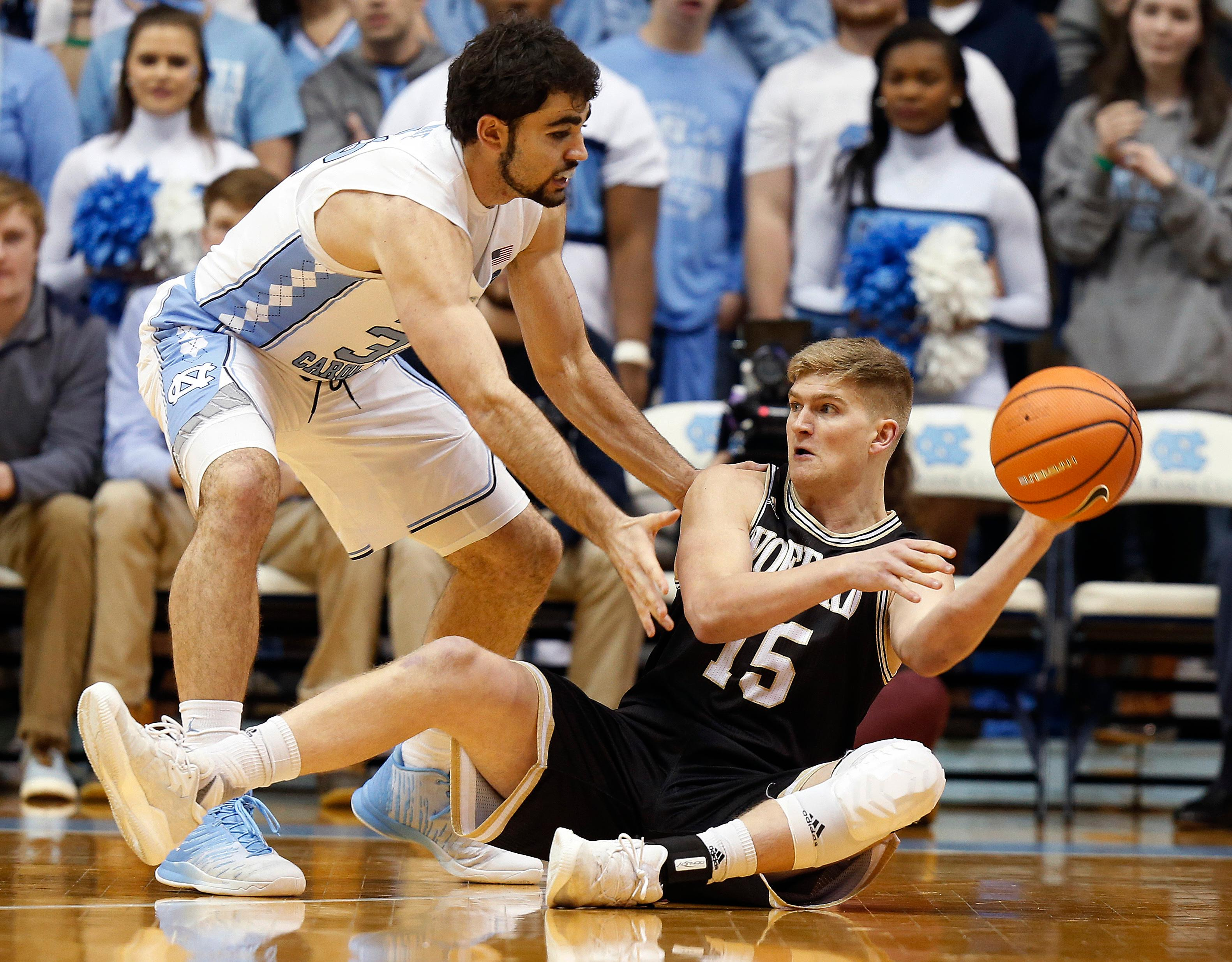 Wofford guard Trevor Stumpe (15) looks to make a pass under pressure from North Carolina forward Luke Maye during the first half of an NCAA college basketball game in Chapel Hill, N.C., Wednesday, Dec. 20, 2017. (AP Photo/Ellen Ozier)