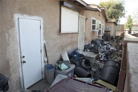 Trash is shown stacked against the home of William Buchman Wednesday Jan. 29, 2014 in Santa Ana, Calif. Buchman has been arrested for investigation of neglect in the care of animals.