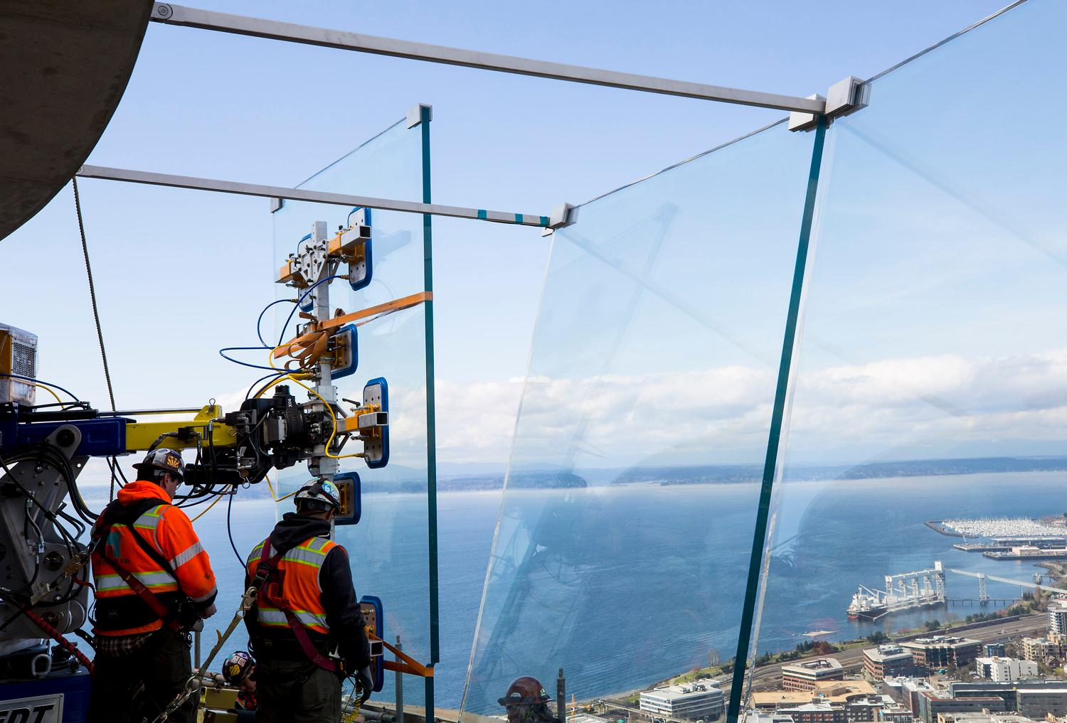 Herzog Glass construction workers use a specially designed machine to suction the 2,300 pound glass panels and place them on the exterior wall of the Observation Deck of the Space Needle, Tuesday, March 20, 2018. A total of 48 glass panels will be installed and are part of the Space Needle's Century Project, a multi-year venture focused on preservation and renovation of the 55-year-old icon. (Sy Bean / Seattle Refined)