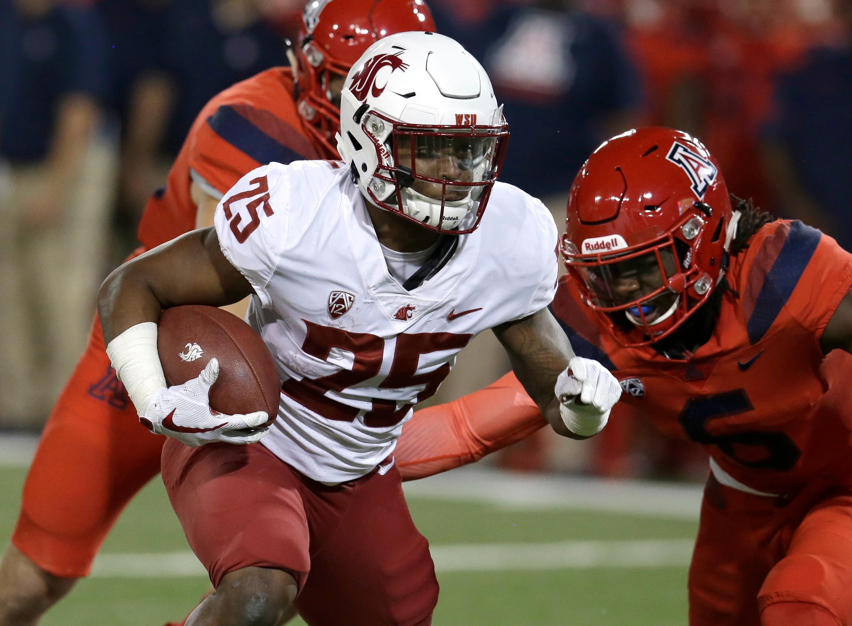 Washington State running back Jamal Morrow (25) runs a way from the tackle of Arizona safety Demetrius Flannigan-Fowles in the first half during an NCAA college football game, Saturday, Oct. 28, 2017, in Tucson, Ariz. (AP Photo/Rick Scuteri)