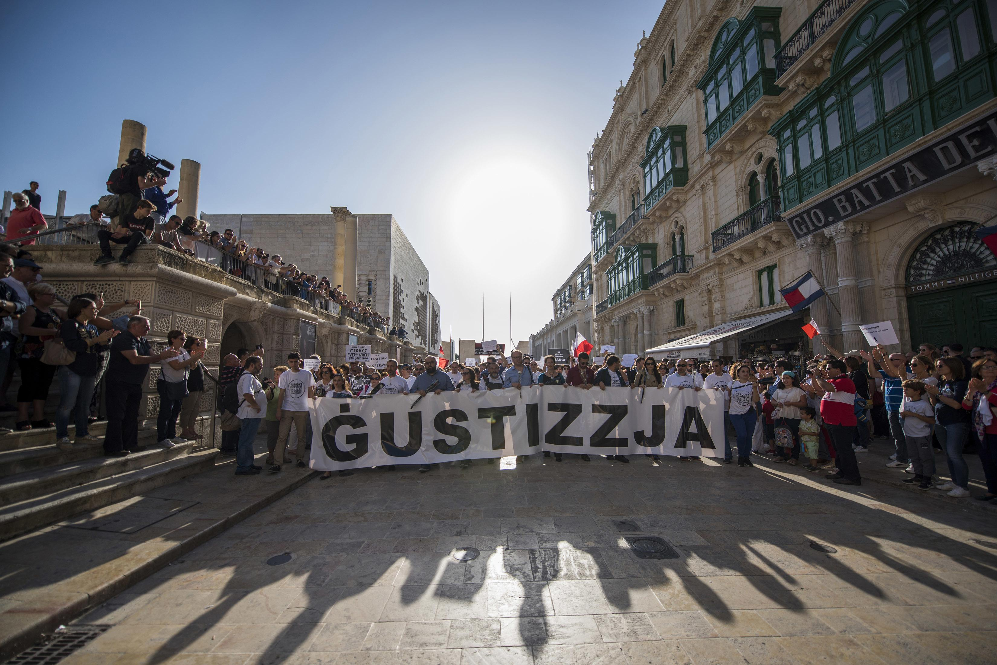 "A banner reading ""justice"" opens a rally in Malta to honor an anti-corruption reporter Daphne Caruana Galizia, killed by a car bomb on Oct. 16, in the capital city of Malta, Valletta, Sunday, Oct. 22, 2017. (AP Photo/Rene Rossignaud)"