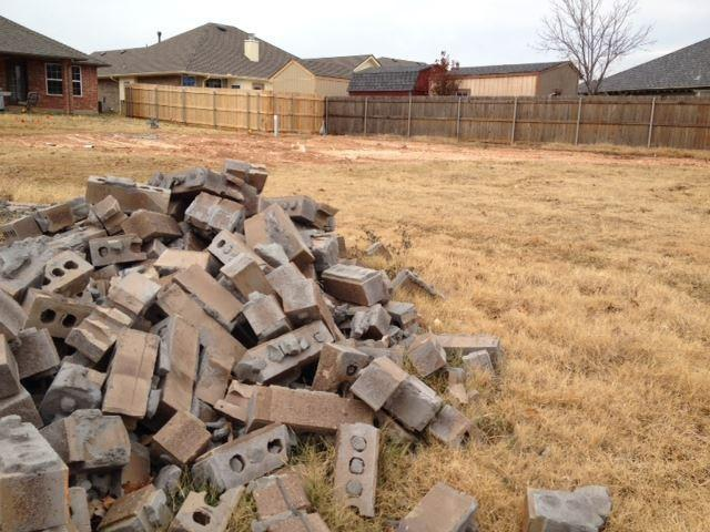 A pile of bricks sits in a neighbor's backyard. Some residents are saving them as mementos.