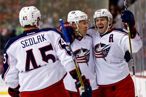 Columbus Blue Jackets center Boone Jenner, right, celebrates scoring a goal with Blue Jackets center Lukas Sedlak (45) and Blue Jackets defenseman Jack Johnson during the first period of an NHL hockey game against the New Jersey Devils, Sunday, March 19, 2017, in Newark, N.J. (AP Photo/Adam Hunger)