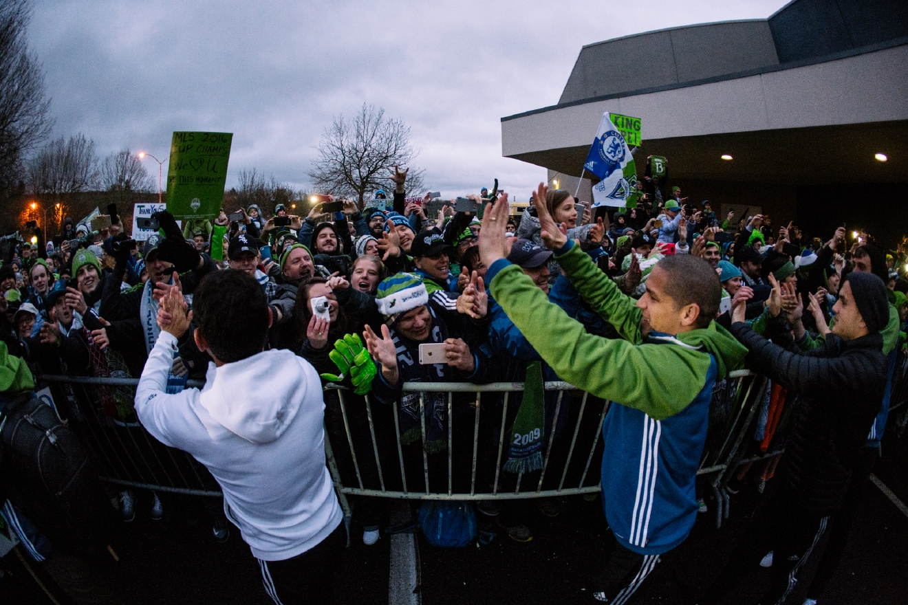 Hundreds of fans gathered at Boeing Field Sunday afternoon (Dec. 11) to greet the MLS champions - the Seattle Sounders - as they returned home from Toronto, where they won the MLS Cup Saturday afternoon in a nail-biting game. Tentatively, there will be an MLS Cup Champions March and Rally in Seattle this Tuesday afternoon (Dec. 13). More info coming soon! (Image: Joshua Lewis / Seattle Refined)