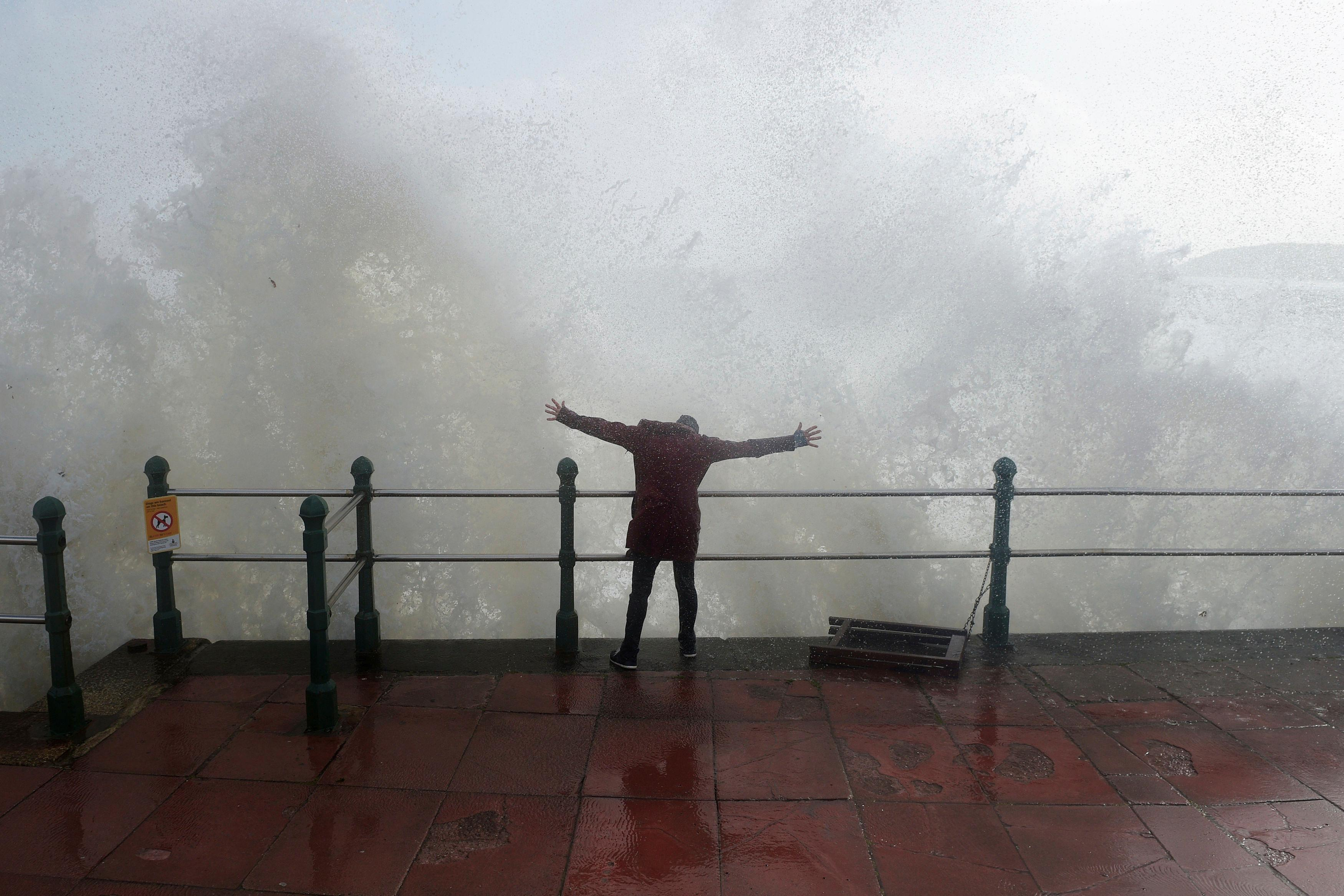 A woman stands as waves crash against the sea wall at Penzanze, Cornwall southwestern England, as the remnants of  Hurricane Ophelia begins to hit parts of Britain and Ireland. Ireland's meteorological service is predicting wind gusts of 120 kph to 150 kph (75 mph to 93 mph), sparking fears of travel chaos. Some flights have been cancelled, and aviation officials are warning travelers to check the latest information before going to the airport Monday.  (Ben Birchall/PA via AP)
