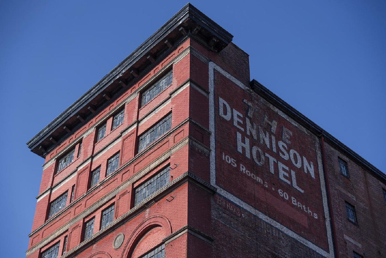 DENNISON HOTEL --> LOCATED IN: Central Business District / BACKGROUND: Originally built as an ironworks factory in 1892 near the NE corner of 7th and Main Streets, it was updated afterward with two more stories and repurposed as a hotel in the 1930s.  It exists as part of the Main Street Historic District, a collective of old buildings protected by law from demolition due to their historic value to the area. // IMAGE: Phil Armstrong