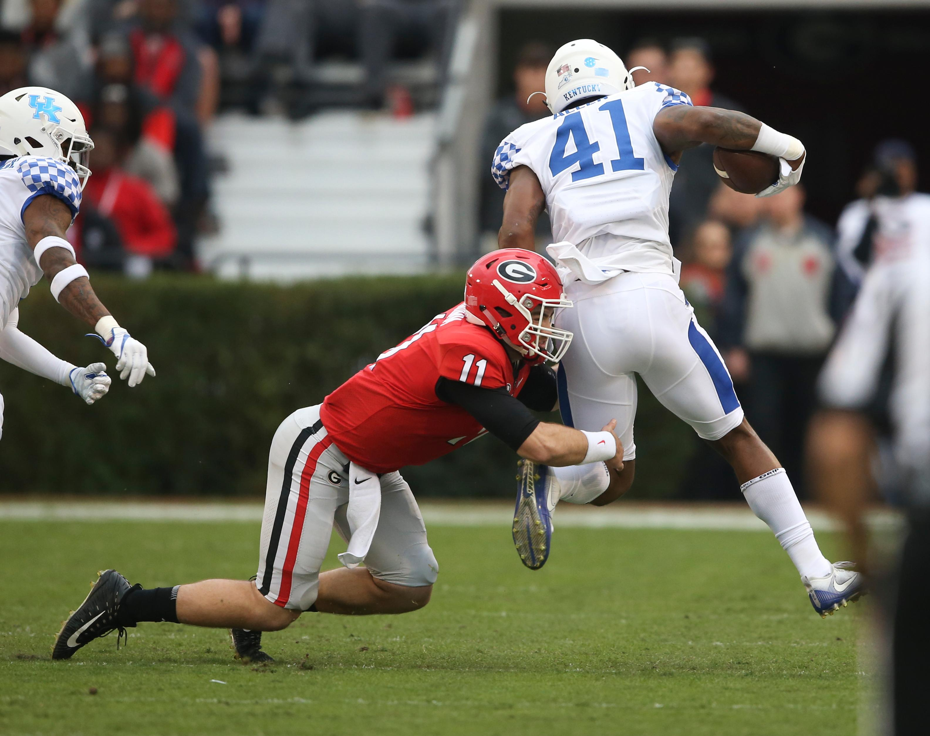 Kentucky linebacker Josh Allen (41) is tackled by Georgia quarterback Jake Fromm (11) after intercepting Fromm's pass in the first half of an NCAA college football game Saturday, Nov. 18, 2017, in Athens, Ga. (AP Photo/John Bazemore)