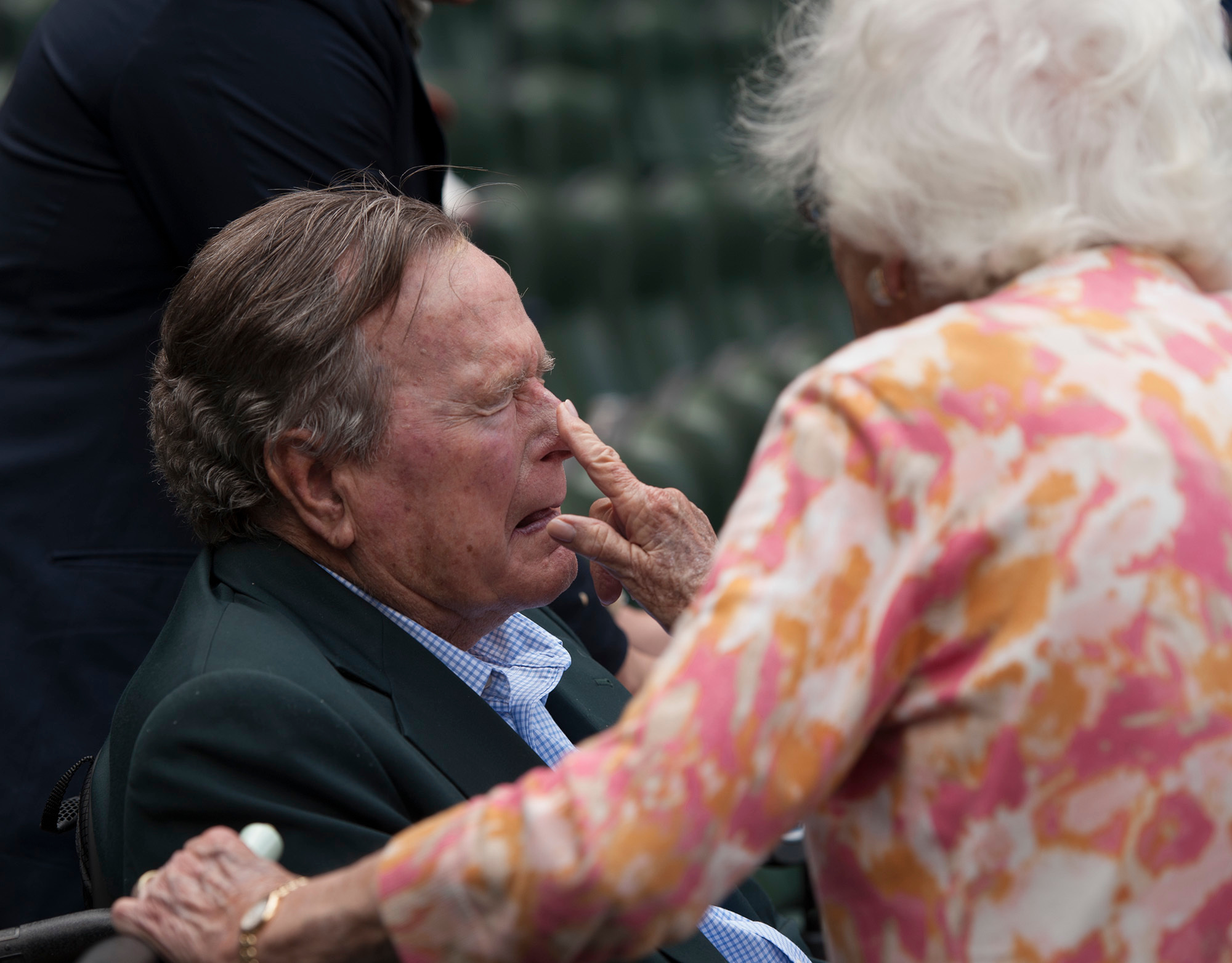 "FILE - In this May 3, 2015, file photo, Barbara Bush applies sunscreen to the nose of her husband, former President George H.W. Bush, before the Seattle Mariners take on the Houston Astros in a baseball game in Houston, Texas. Former first couple George and Barbara Bush's relationship is a true love story, described by granddaughter Jenna Bush Hager as ""remarkable."" They met at a Christmas dance. She was 17. He was 18. Two years later they were married. Now 73 years later, with Barbara Bush declining further medical care for health problems, they are the longest-married couple in presidential history. (AP Photo/George Bridges, File)"