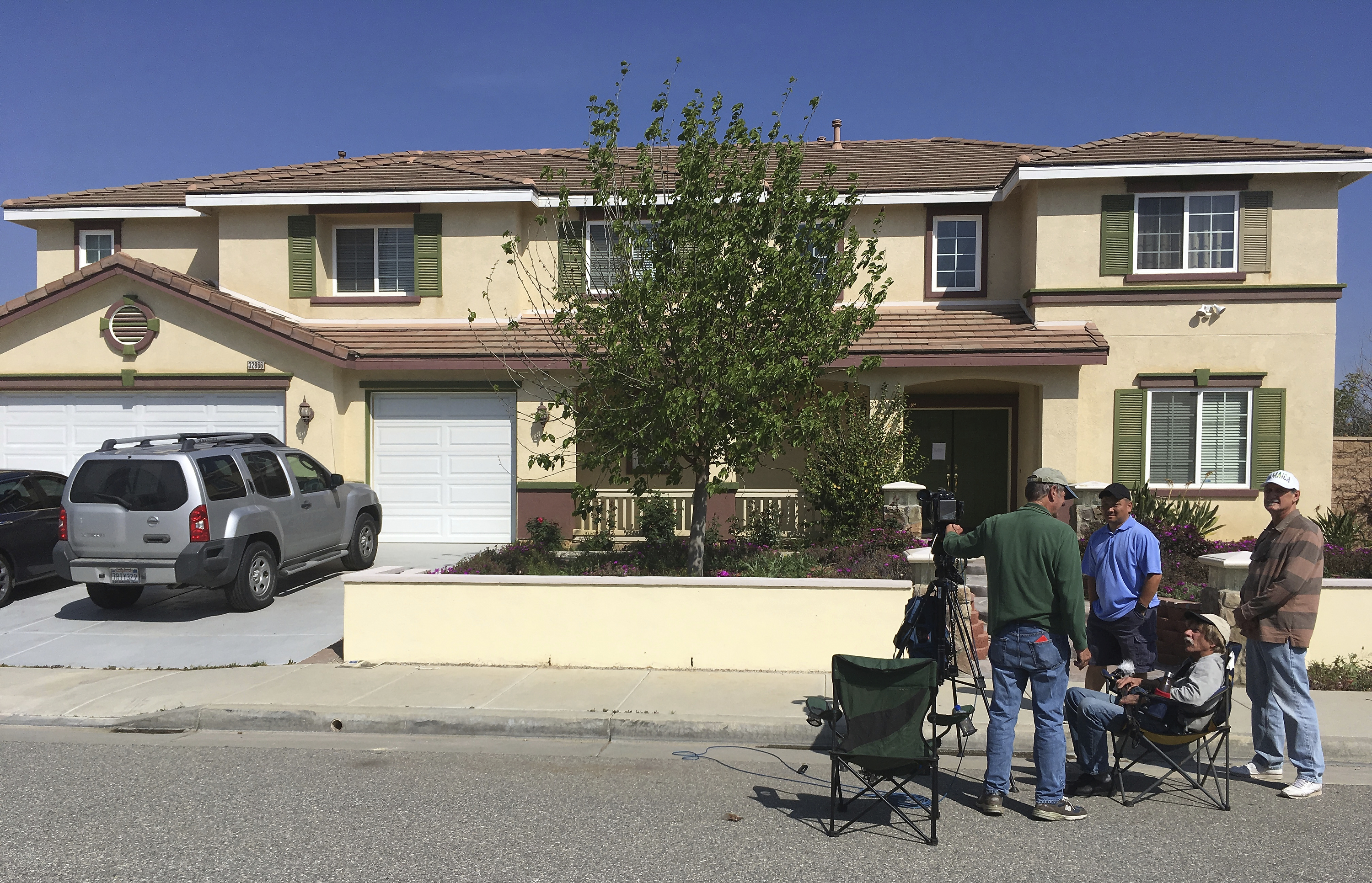 Members of the media stand outside the home of the YouTube shooter's parents in Menifee, Calif., Wednesday, April 4, 2018. The shooter, Nasim Aghdam, had lived in Menifee, Calif., southeast of Los Angeles about five years ago. (AP Photo/Elliot Spagat)