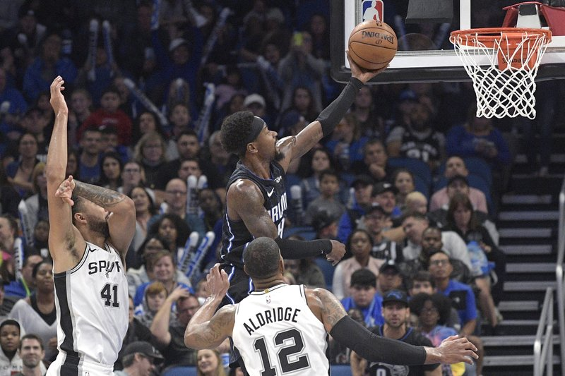 Orlando Magic guard Terrence Ross goes up to shoot in front of San Antonio Spurs center Trey Lyles (41) and forward LaMarcus Aldridge (12) during the second half of an NBA basketball game Friday, Nov. 15, 2019, in Orlando, Fla. (AP Photo/Phelan M. Ebenhack)