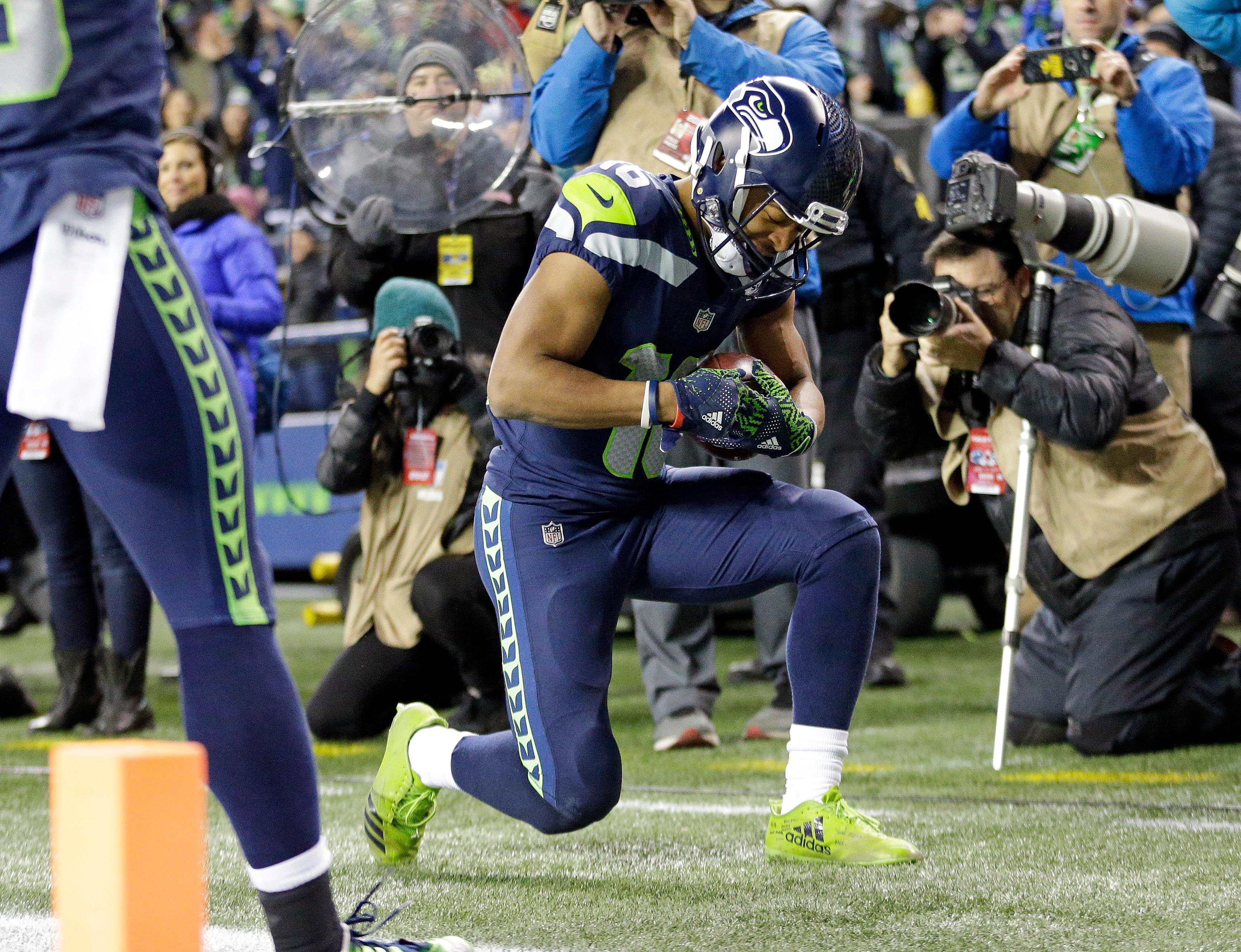 Seattle Seahawks' Tyler Lockett kneels after scoring a touchdown against the Philadelphia Eagles during the second half of an NFL football game, Sunday, Dec. 3, 2017, in Seattle. (AP Photo/Ted S. Warren)