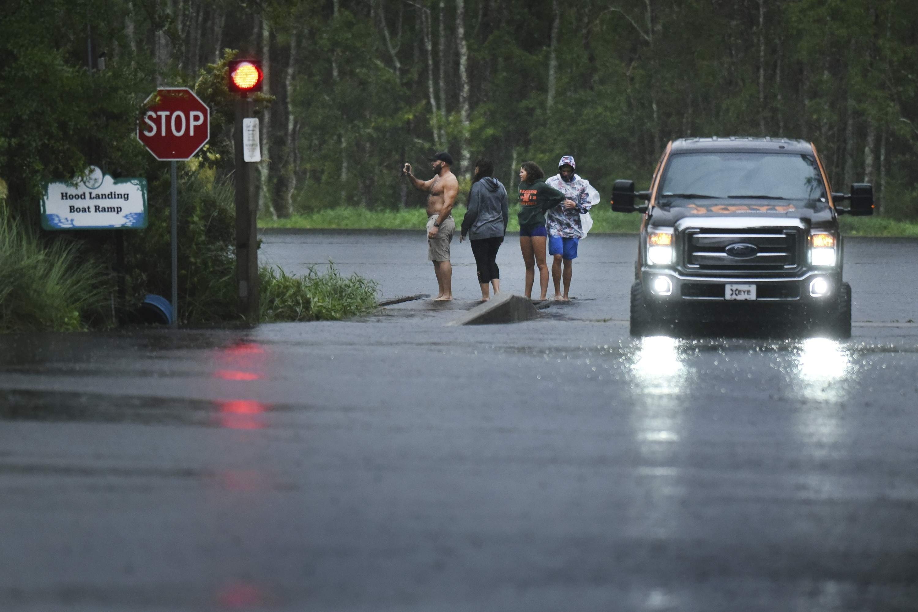 Occupants in a pickup truck get out to look at the rain swollen Julington Creek at the flooded boat ramp on Hood Landing Road by Clark's Fish Camp in Jacksonville, Fla., Sunday evening, Sept. 10, 2017, as Hurricane Irma passes the area. (Bob Self/The Florida Times-Union via AP)
