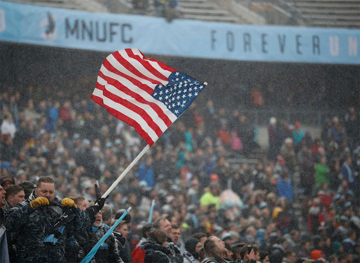 A fan waveds a flag during the national anthem at an MLS soccer game between Atlanta United and Minnesota United, Sunday, March 12, 2017, in Minneapolis, Minn. (Jeff Wheeler/Star Tribune via AP)