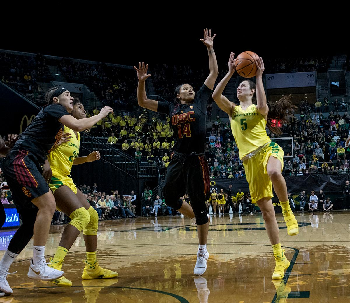 Oregon Ducks Maite Cazorla (#5) aims for the basket as USC Trojans Sadie Edwards (#14) attempts to block the shot. The Oregon Ducks defeated the USC Trojans 80-74 on Friday at Matthew Knight Arena in a game that went into double overtime. Lexi Bando sealed the Ducks' victory by scoring a three-pointer in the closing of the game. Ruthy Hebard set a new NCAA record of 30 consecutive field goals in three straight games, the old record being 28. Ruthy Hebard got a double-double with 27 points and 10 rebounds, Mallory McGwire also had 10 rebounds. The Ducks had four players in double digits. The Ducks are now 24-4, 13-2 in the Pac-12, and are tied for first with Stanford. Photo By Rhianna Gelhart, Oregon News Lab