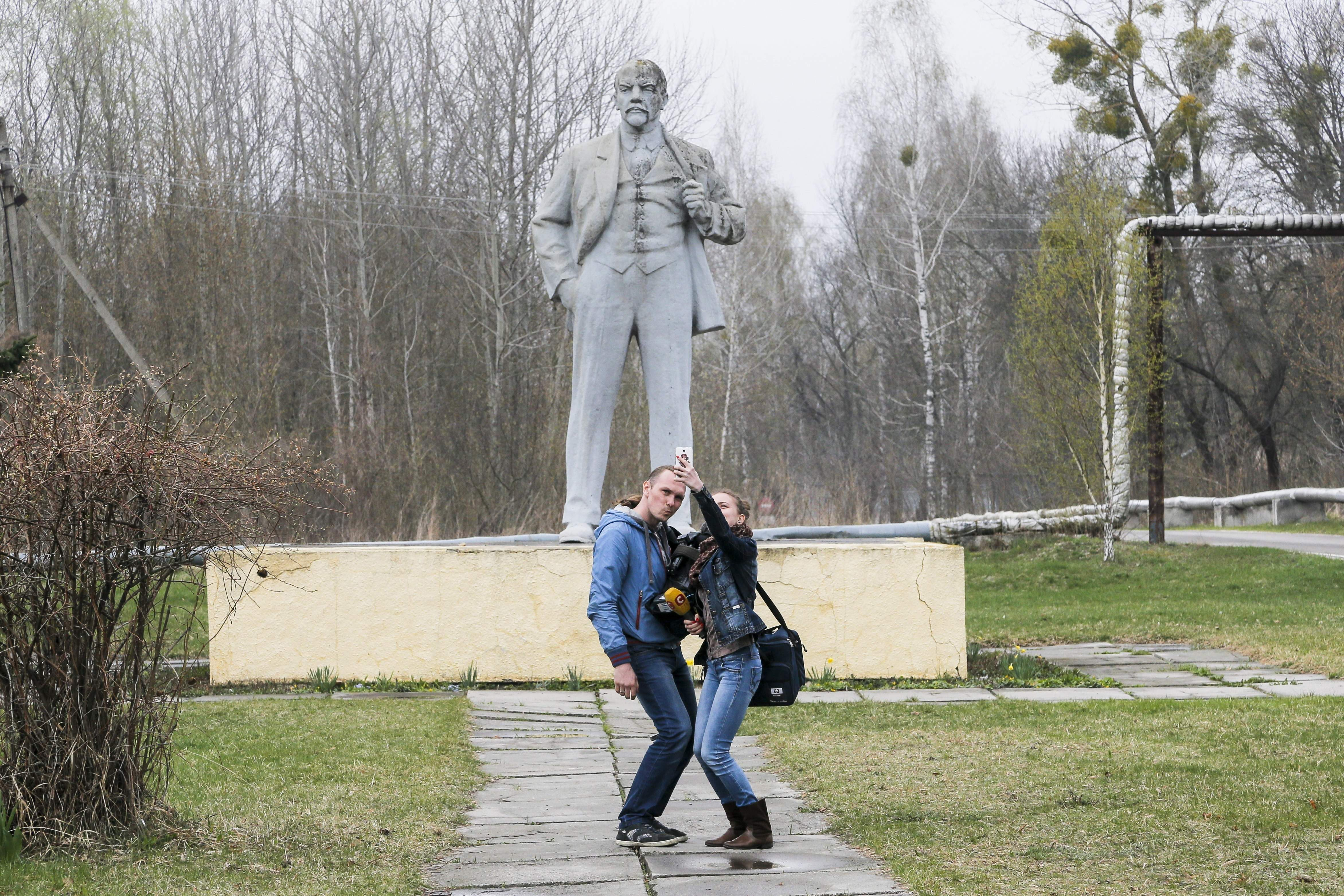 In this photo taken Wednesday, April 5, 2017, journalists take a selfie in front of the monument of Soviet state founder Vladimir Lenin in Chernobyl, Ukraine. April 26 marks the 31st anniversary of the Chernobyl nuclear disaster. A reactor at the Chernobyl nuclear power plant exploded on April 26, 1986, leading to an explosion and the subsequent fire spewed a radioactive plume over much of northern Europe. THE ASSOCIATED PRESS