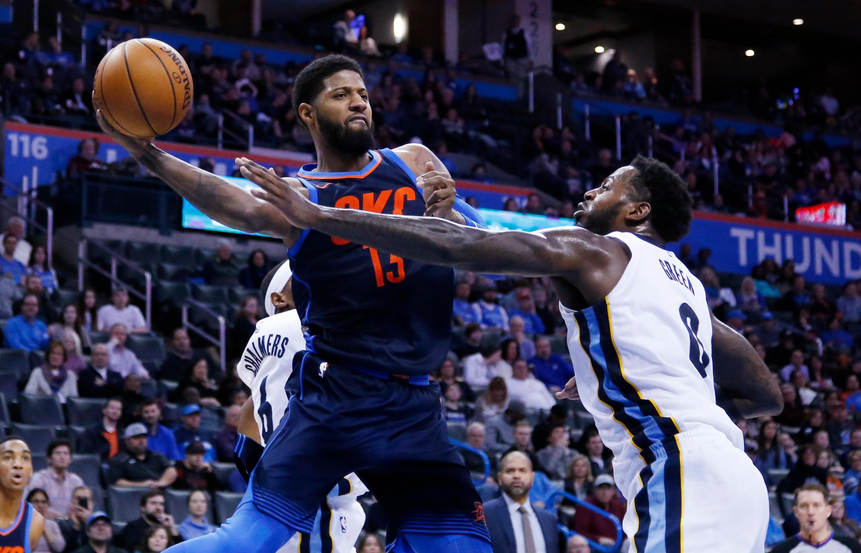 Oklahoma City Thunder forward Paul George (13) passes around Memphis Grizzlies forward JaMychal Green (0) in the second half of an NBA basketball game in Oklahoma City, Sunday, Feb. 11, 2018. (AP Photo/Sue Ogrocki)
