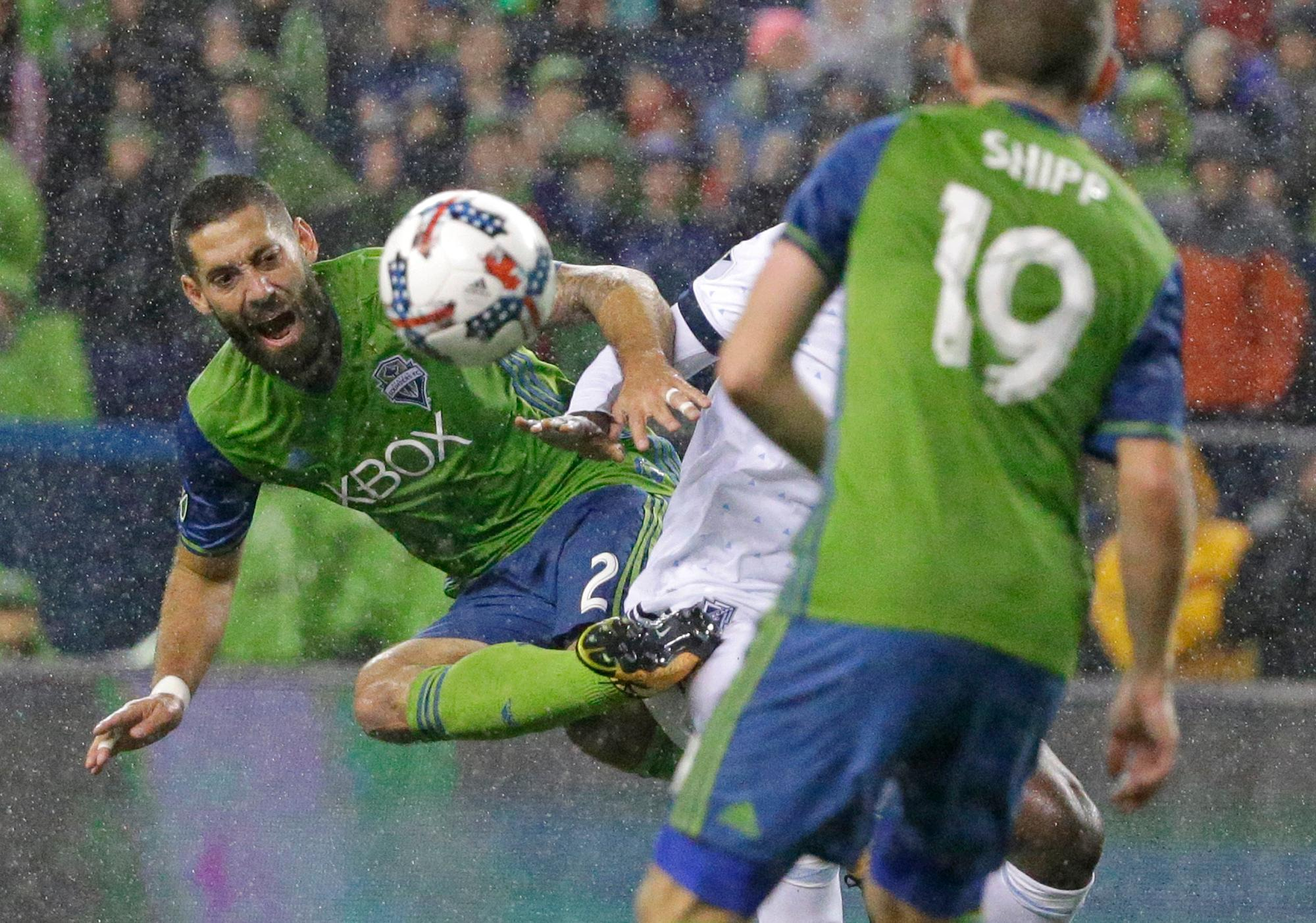 Seattle Sounders midfielder Clint Dempsey, left, kicks the ball away from Vancouver Whitecaps midfielder Aly Ghazal as Sounders' Harrison Shipp (19) looks on during the first half of the second leg of an MLS soccer Western Conference semifinal, Thursday, Nov. 2, 2017, in Seattle. (AP Photo/Ted S. Warren)
