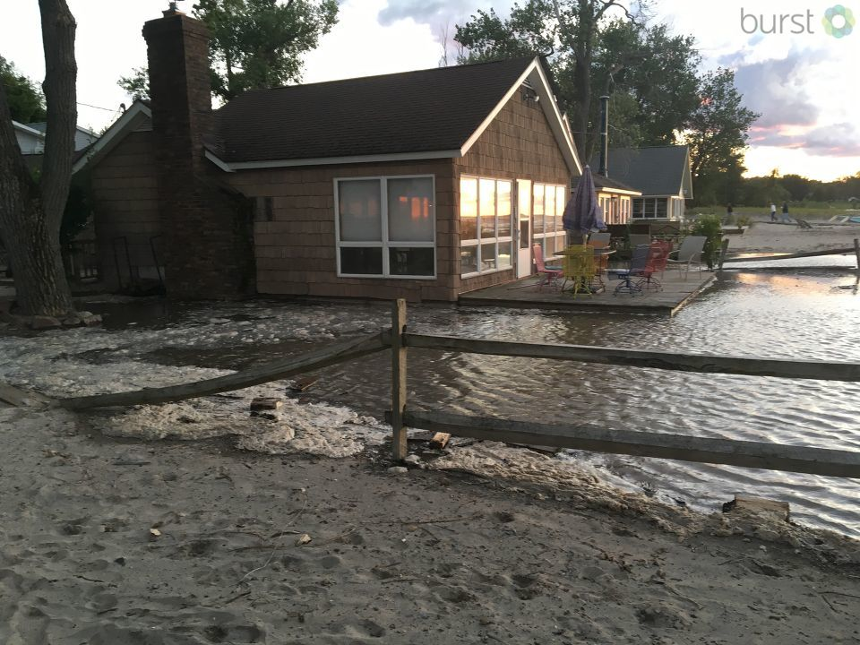 Homes along the shoreline are flooded after high speed winds cause huge waves to crash along the shore of Sodus Point.