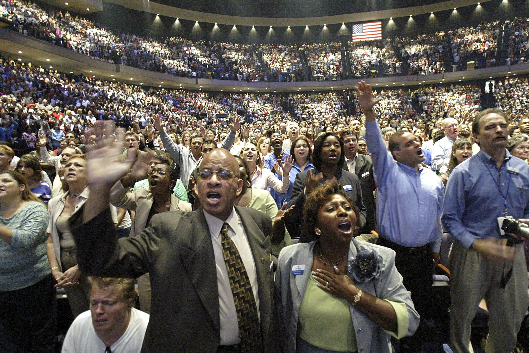 FILE - In this July 16, 2005, file photo, members of the Lakewood Church worship at the grand opening of their megachurch in Houston. Lakewood pastor Joel Osteen said in a statement to ABC News on Aug. 28, 2017, that his massive church would open as a shelter for Hurricane Harvey victims if needed. (AP Photo/Jessica Kourkounis, File)