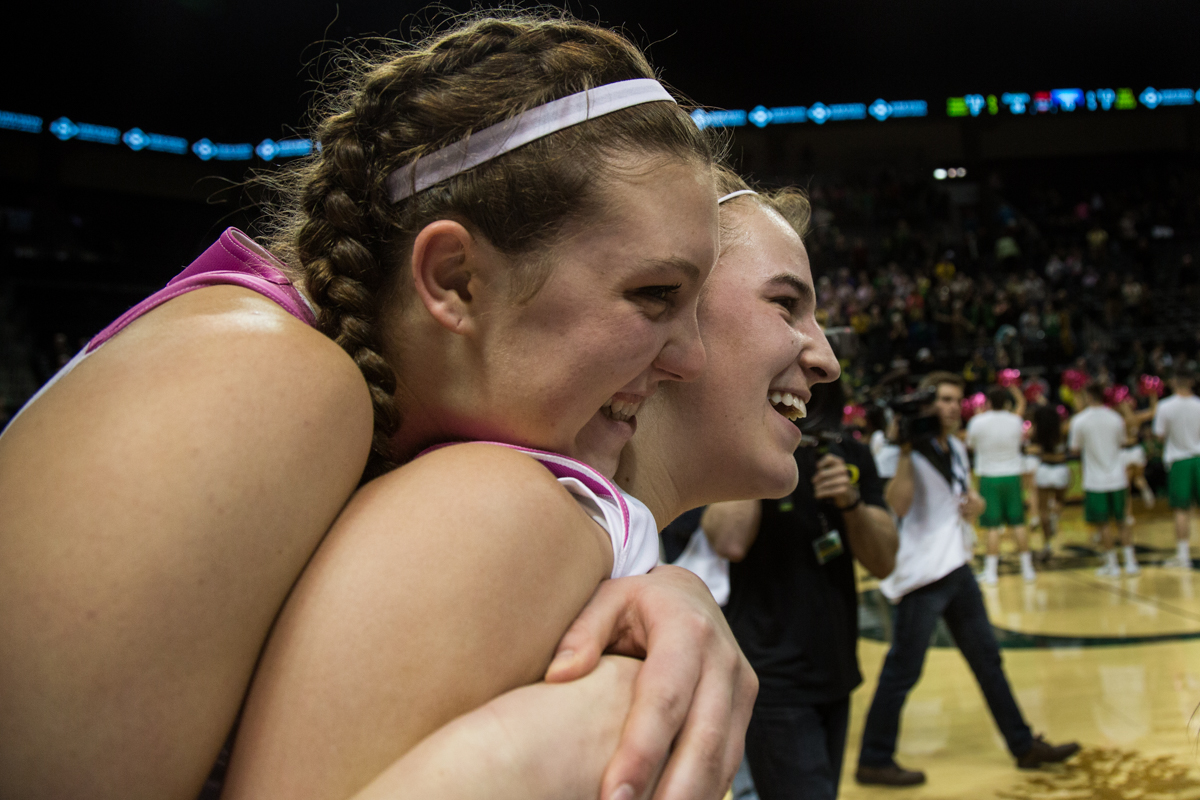 Oregon Ducks Sierra Campisano (#52) hugs teammate Sabrina Ionescu (#20) after their upset win over the UCLA Bruins. The Oregon Ducks defeated the No. 15 UCLA Bruins 84-75 Friday evening at Matthew Knight Arena in Eugene, Oregon.  Photo by Austin Hicks, Oregon News Lab