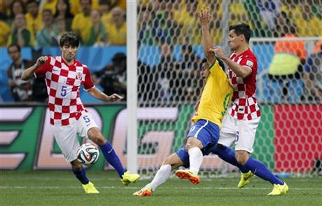 Brazil's Fred, center, falls next to Croatia's Dejan Lovren, right, as Croatia's Vedran Corluka, left, watches during the group A World Cup soccer match in the opening game of the tournament at Itaquerao Stadium in Sao Paulo, Brazil, Thursday, June 12, 20