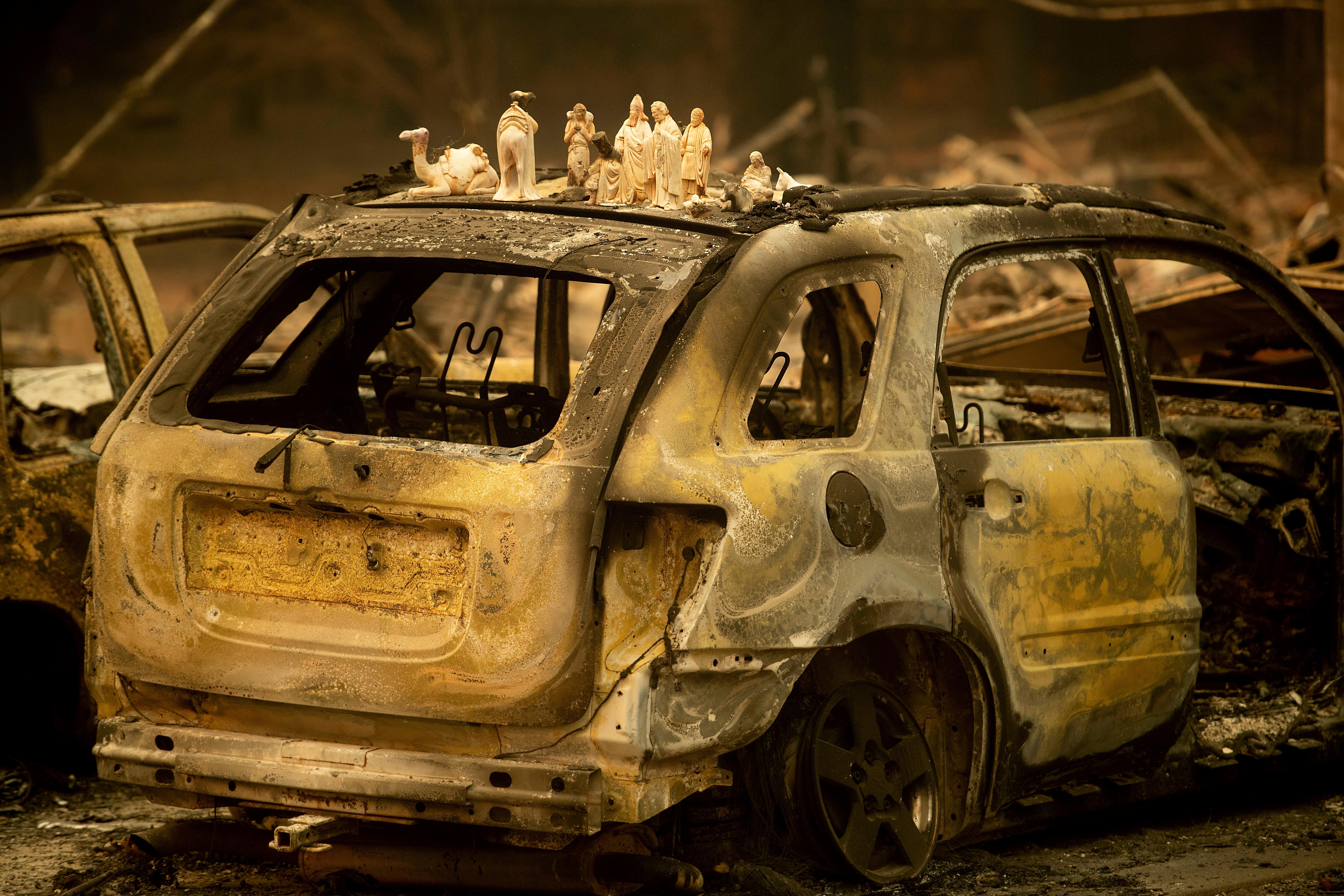 Following the Camp Fire, figurines rest atop a scorched car on Pearson Road, Monday, Nov. 12, 2018, in Paradise, Calif. (AP Photo/Noah Berger)