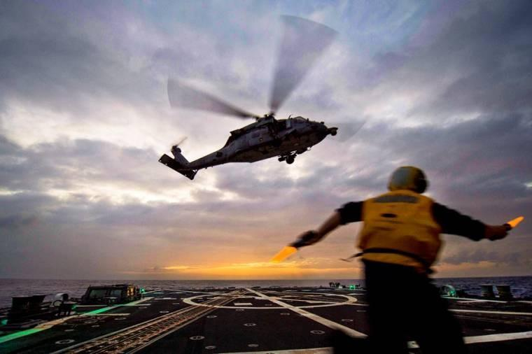U.S. Navy Petty Officer 3rd Class Robert Barnes signals to an MH-60S Seahawk helicopter from Helicopter Sea Combat Squadron 12 during flight operations aboard the guided-missile destroyer USS Mustin in the South China Sea.