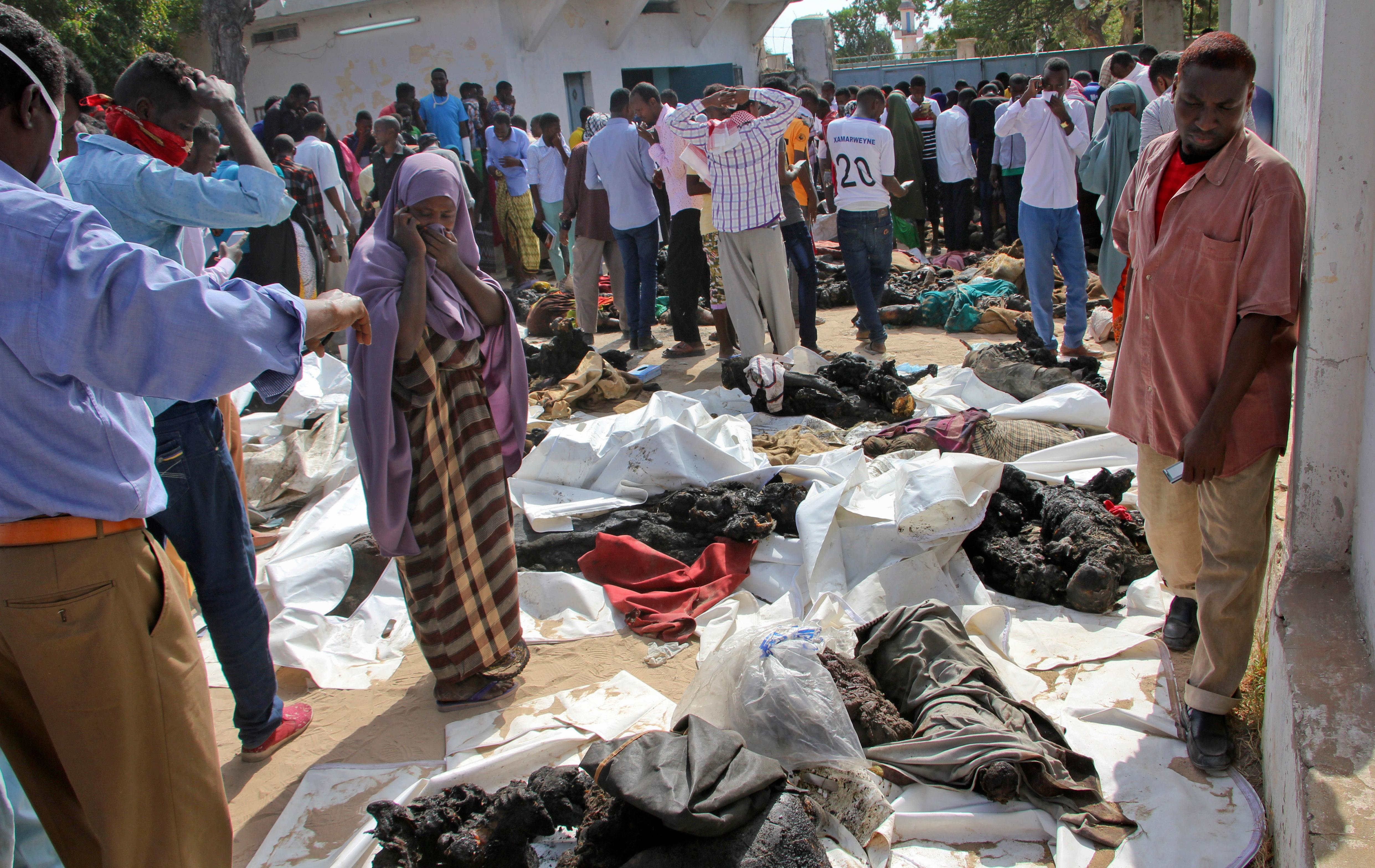 EDS NOTE: GRAPHIC CONTENT. A Somali woman reacts as she stands by the remains of victims of Saturday's blast, in Mogadishu, Somalia, Sunday, Oct. 15, 2017.  The death toll from the most powerful bomb blast witnessed in Somalia's capital rose Sunday to at least 189 with more than 200 injured, making it the deadliest single attack ever in the Horn of Africa nation, police and hospital sources said. (AP Photo/Farah Abdi Warsameh)