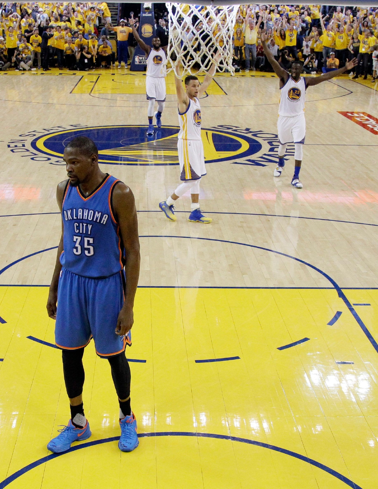 Oklahoma City Thunder's Kevin Durant (35) stands under the basket as the Golden State Warriors celebrate a score during the first half in Game 2 of the NBA basketball Western Conference finals Wednesday, May 18, 2016, in Oakland, Calif. Golden State won 118-91. (AP Photo/Marcio Jose Sanchez)