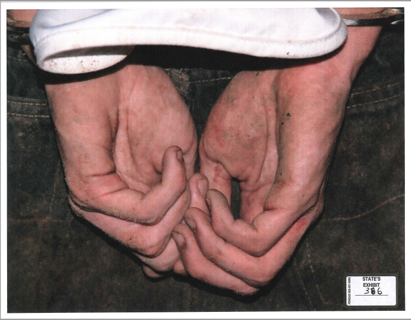 A close-up of Robert Bever's hands after his arrest for killing his parents and three siblings. (KTUL)