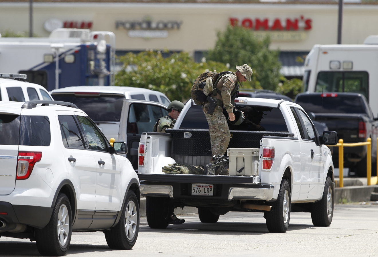 A police officer in tactical gear sets up in a parking lot while responding a police shooting near Old Hammond Highway and Drusilla Lane in Baton Rouge on Sunday, July 17, 2016. Multiple law enforcement officers were killed and wounded Sunday morning in a shooting near a gas station in Baton Rouge, less than two weeks after a black man was shot and killed by police here, sparking nightly protests across the city. (Chris Grange/NOLA.com The Times-Picayune via AP)