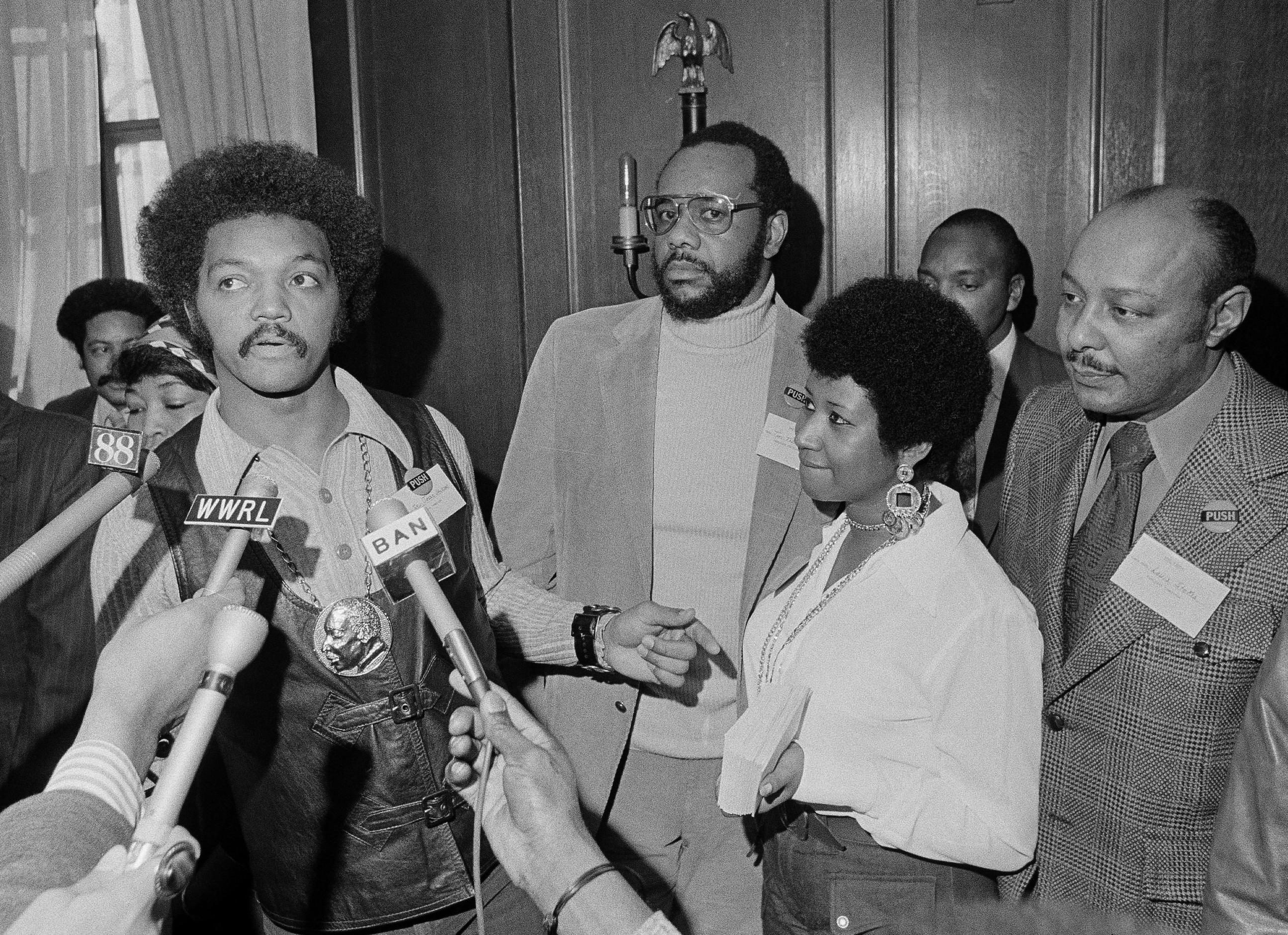 This March 26, 1972 file photo shows the Rev. Jesse Jackson speaking to reporters at the Operation PUSH Soul Picnic in New York as Tom Todd, vice president of PUSH, from second left, Aretha Franklin and Louis Stokes. Franklin died Thursday, Aug. 16, 2018 at her home in Detroit.  She was 76. (AP Photo/Jim Wells, File)