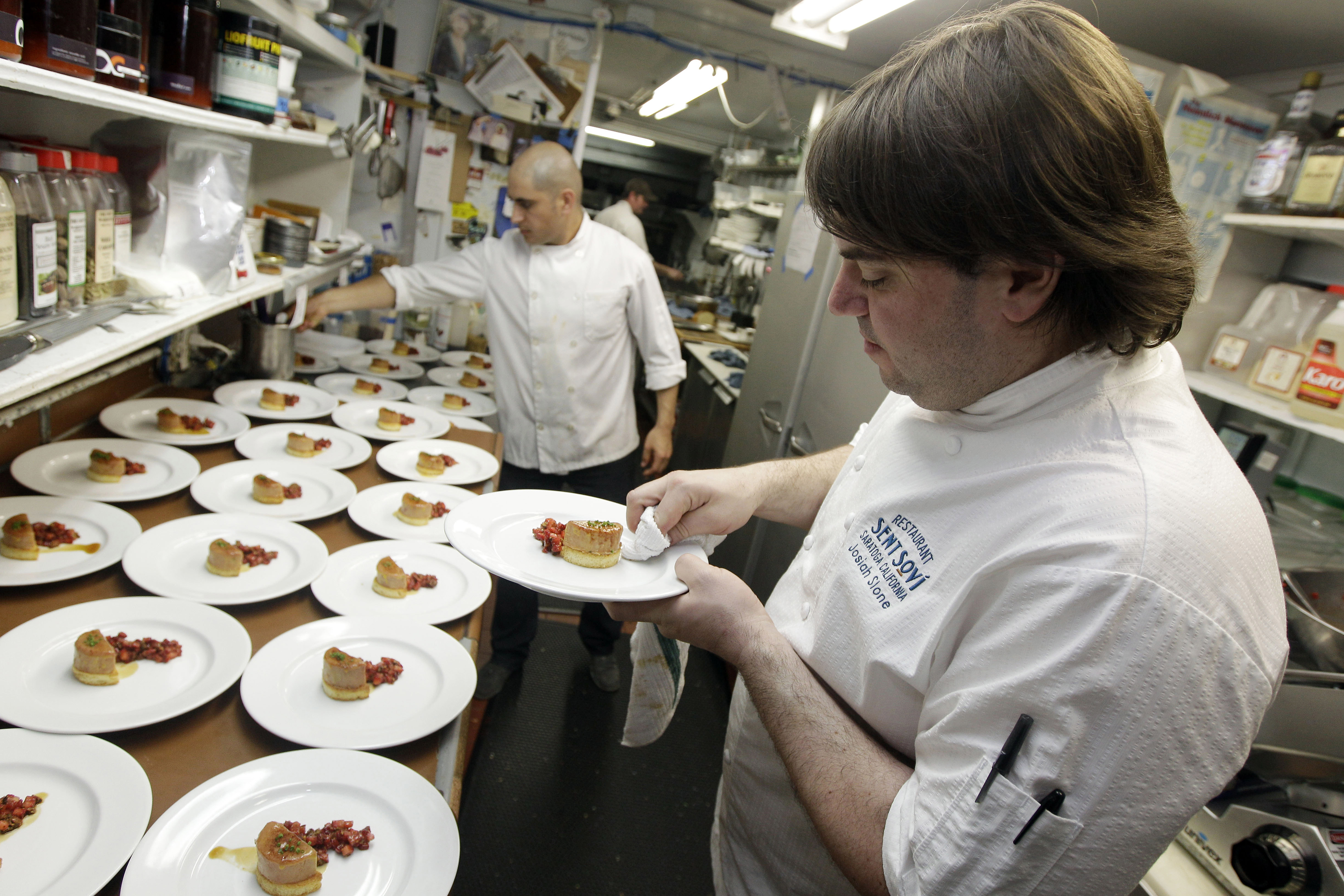 FILE - In this May 11, 2012, file photo, chef and owner Josiah Slone, right, prepares a foie gras dish at Sent Sovi restaurant in Saratoga, Calif. The Presidio Social Club restaurant is on federal land, so it's exempt from the restriction.  (AP Photo/Marcio Jose Sanchez, File)