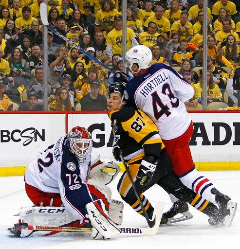Pittsburgh Penguins' Sidney Crosby (87) is hit by Columbus Blue Jackets' Scott Hartnell (43) as he gets off a shot in front of goalie Sergei Bobrovsky (72) during the second period in Game 2 of an NHL first-round hockey playoff series in Pittsburgh, Friday, April 14, 2017. (AP Photo/Gene J. Puskar)