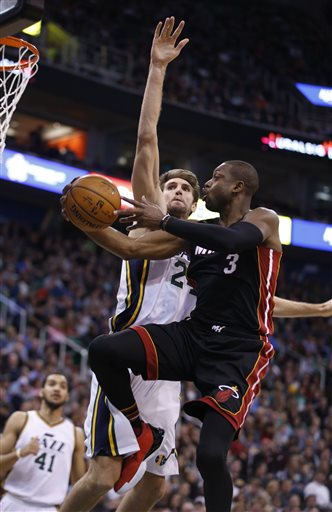 Miami Heat guard Dwyane Wade, right, lays a shot in past Utah Jazz center Jeff Withey, left, during an NBA basketball game Saturday, Jan. 9, 2016, in Salt Lake City. (AP Photo/George Frey)