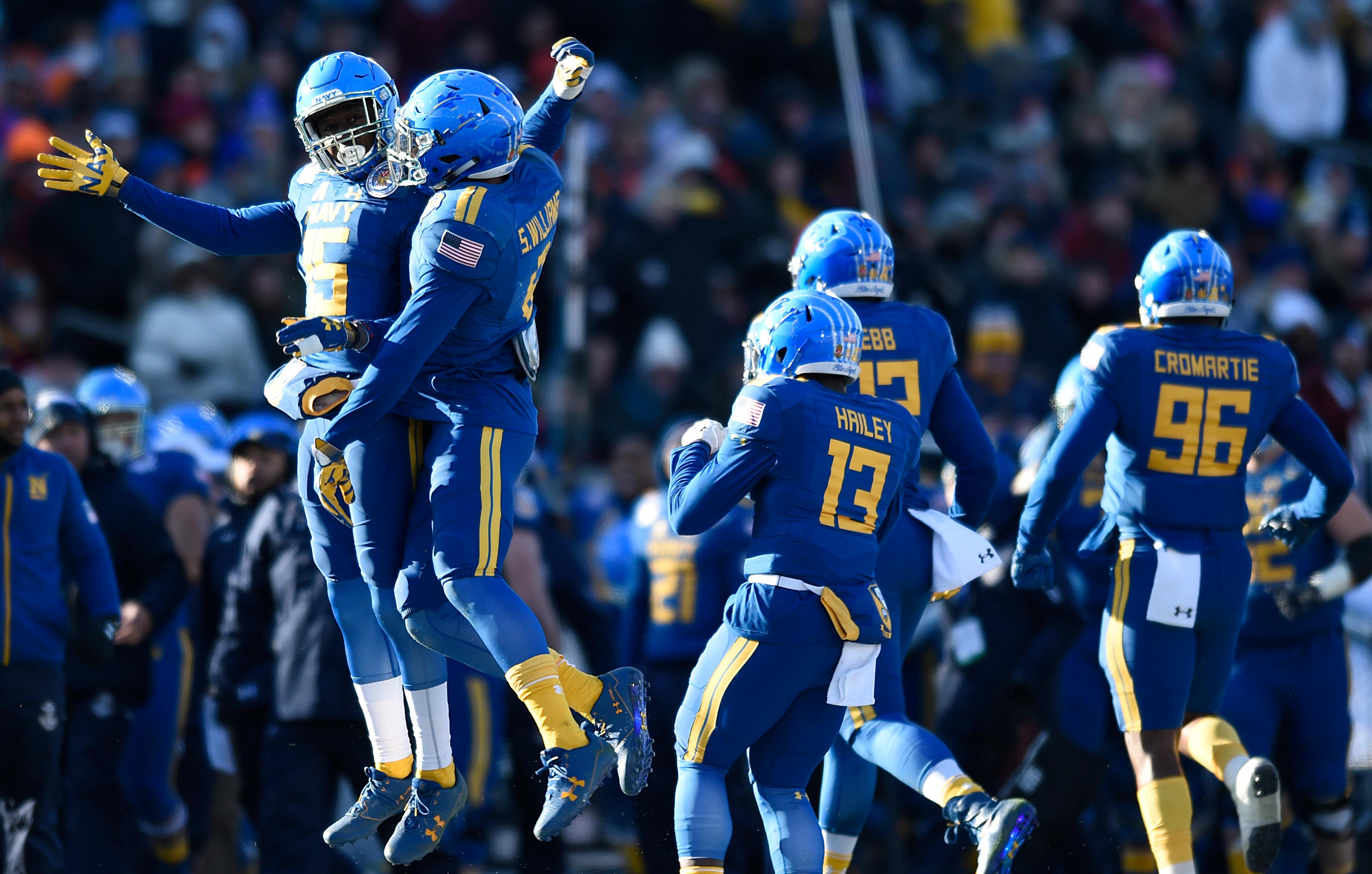 Navy's Justin Norton, left, and Sean Williams, center, jump in the air to celebrate Williams interception against Virginia in the first half of the Military Bowl NCAA college football game, Thursday, Dec. 28, 2017, in Annapolis, Md. (AP Photo/Gail Burton)