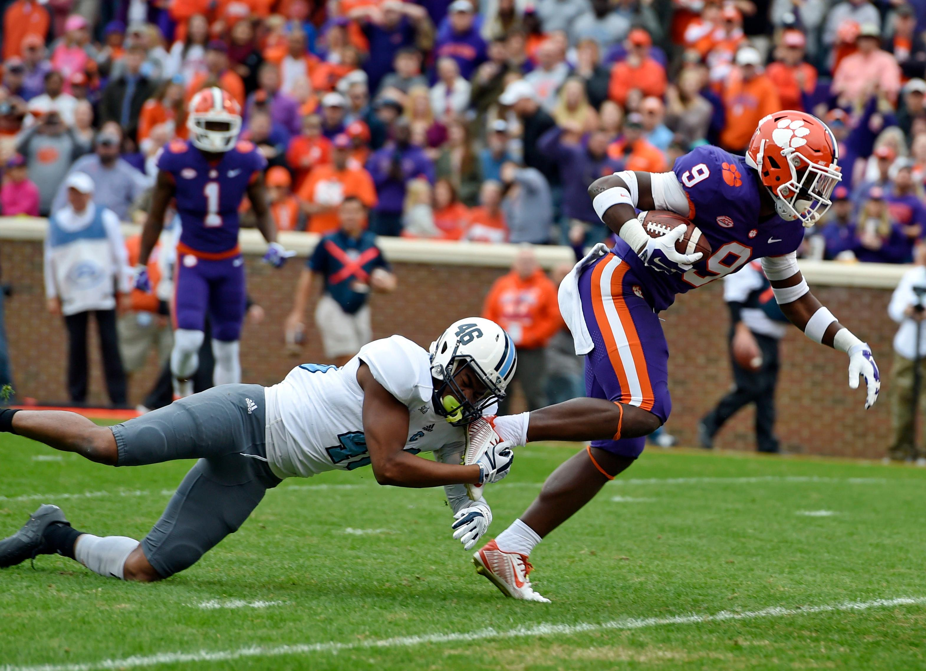 Clemson's Travis Etienne (9) slips the tackle attempt of Citadel's Carl Cunningham Jr. to score a touchdown during the first half of an NCAA college football game Saturday, Nov. 18, 2017, in Clemson, S.C. (AP Photo/Richard Shiro)